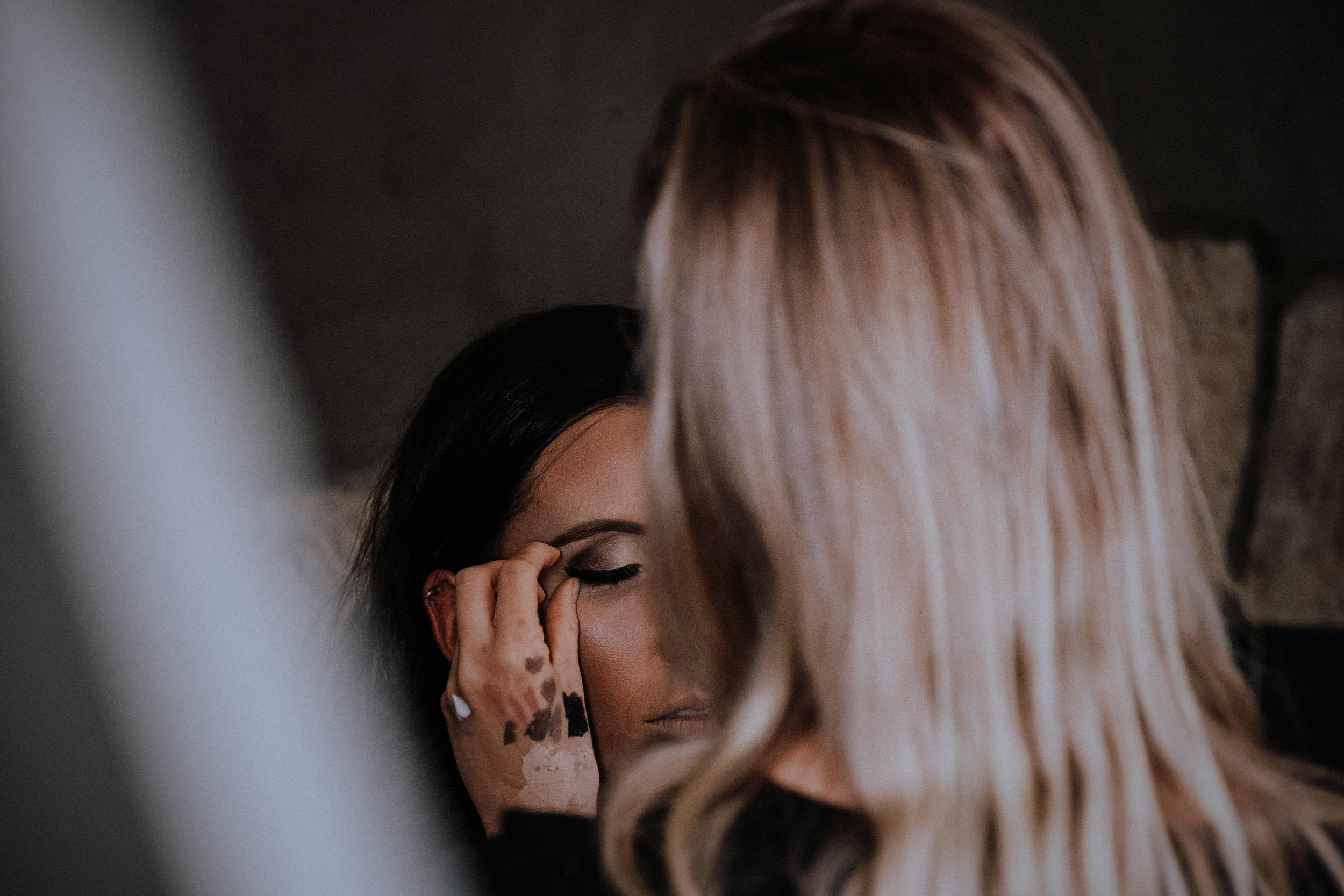A bride having her makeup done getting ready before her wet and rainy wedding