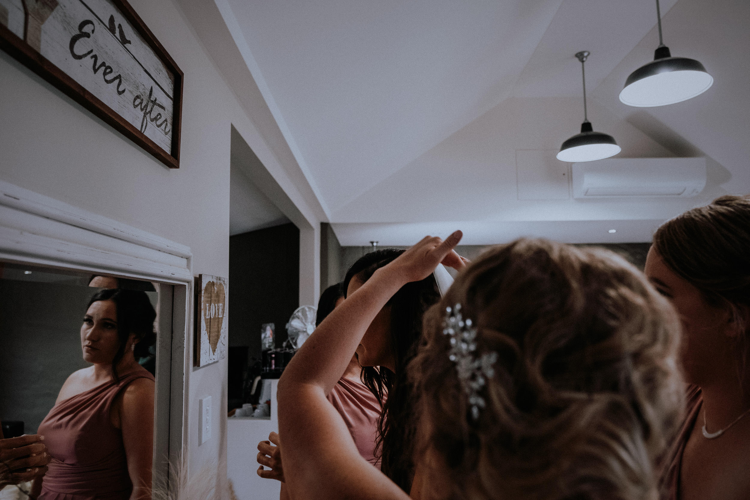 A photojournalistic candid shot of bride and bridesmaids getting ready for the wedding
