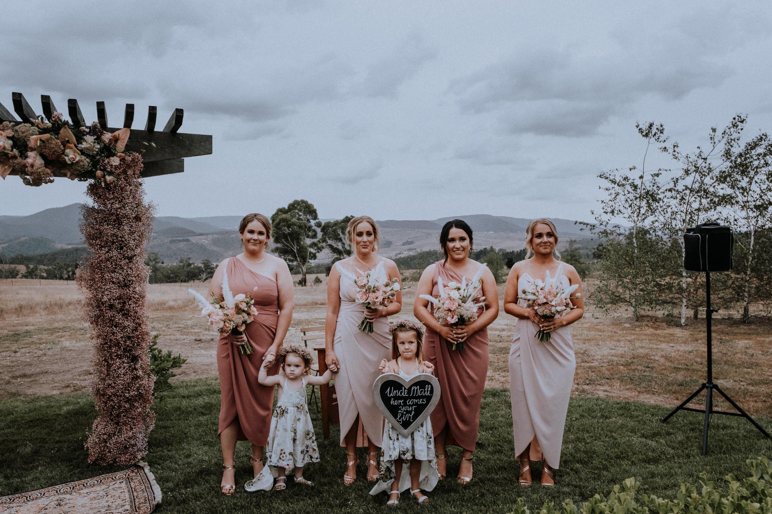 Bridesmaids await bride walking down the aisle