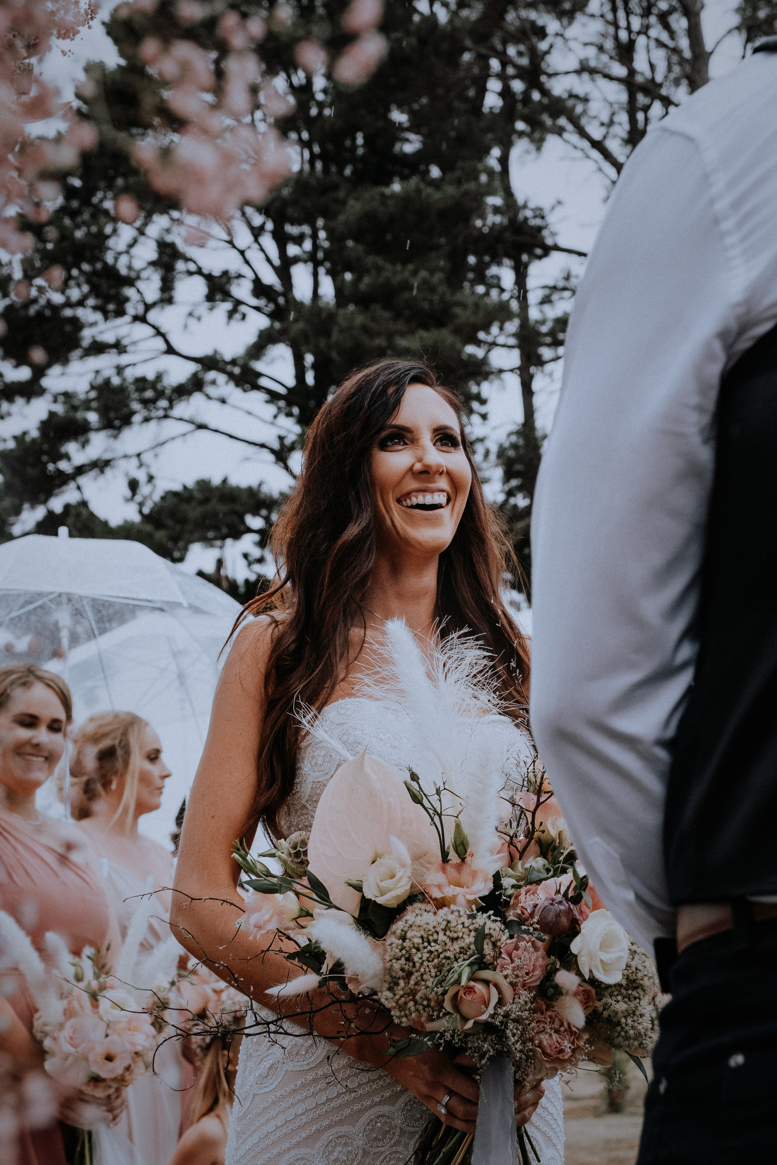 An ecstatic bride during her rainy outdoor wedding at Seclusions Blue Mountains