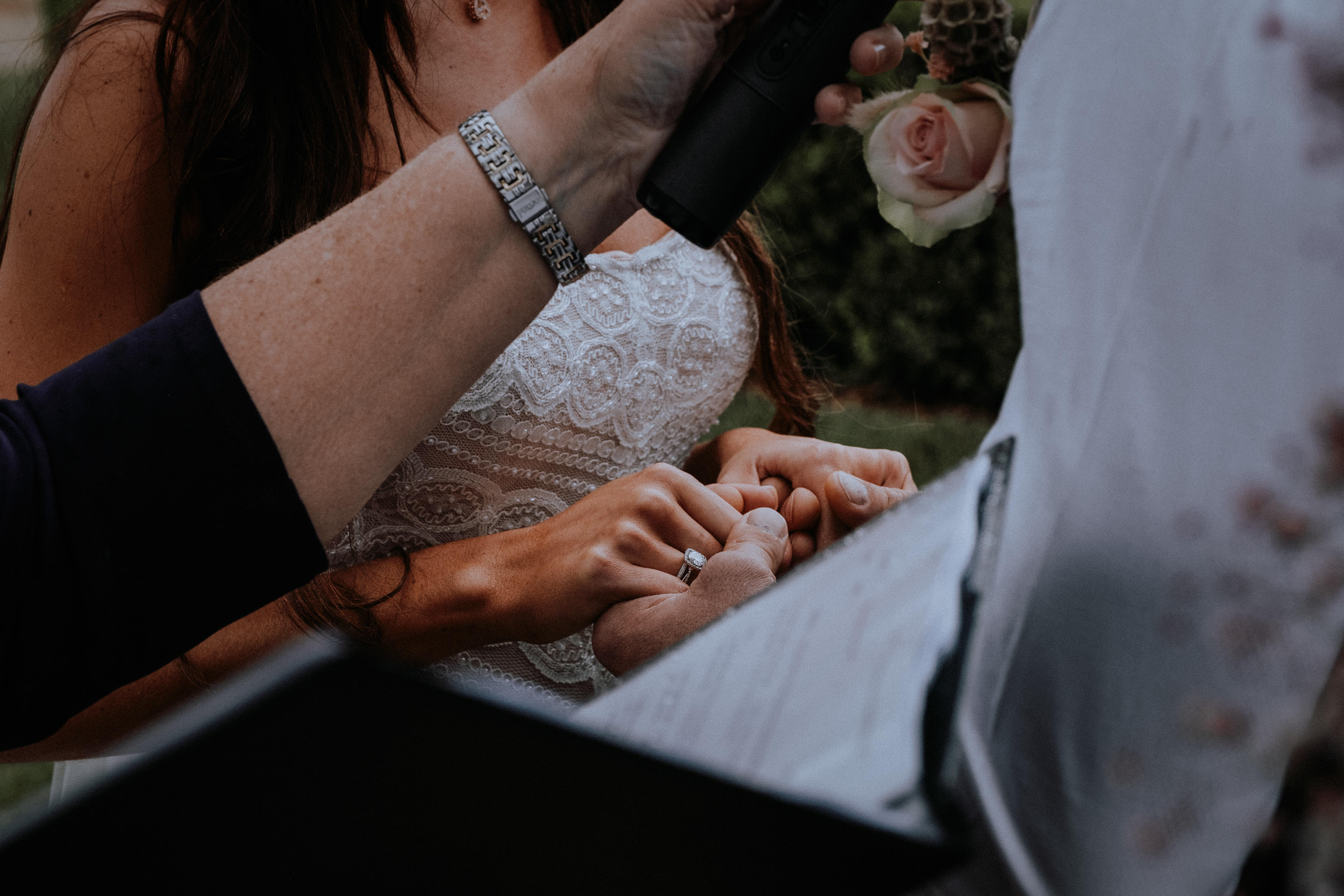 A close up on a bride and groom holding hands during their wedding ceremony