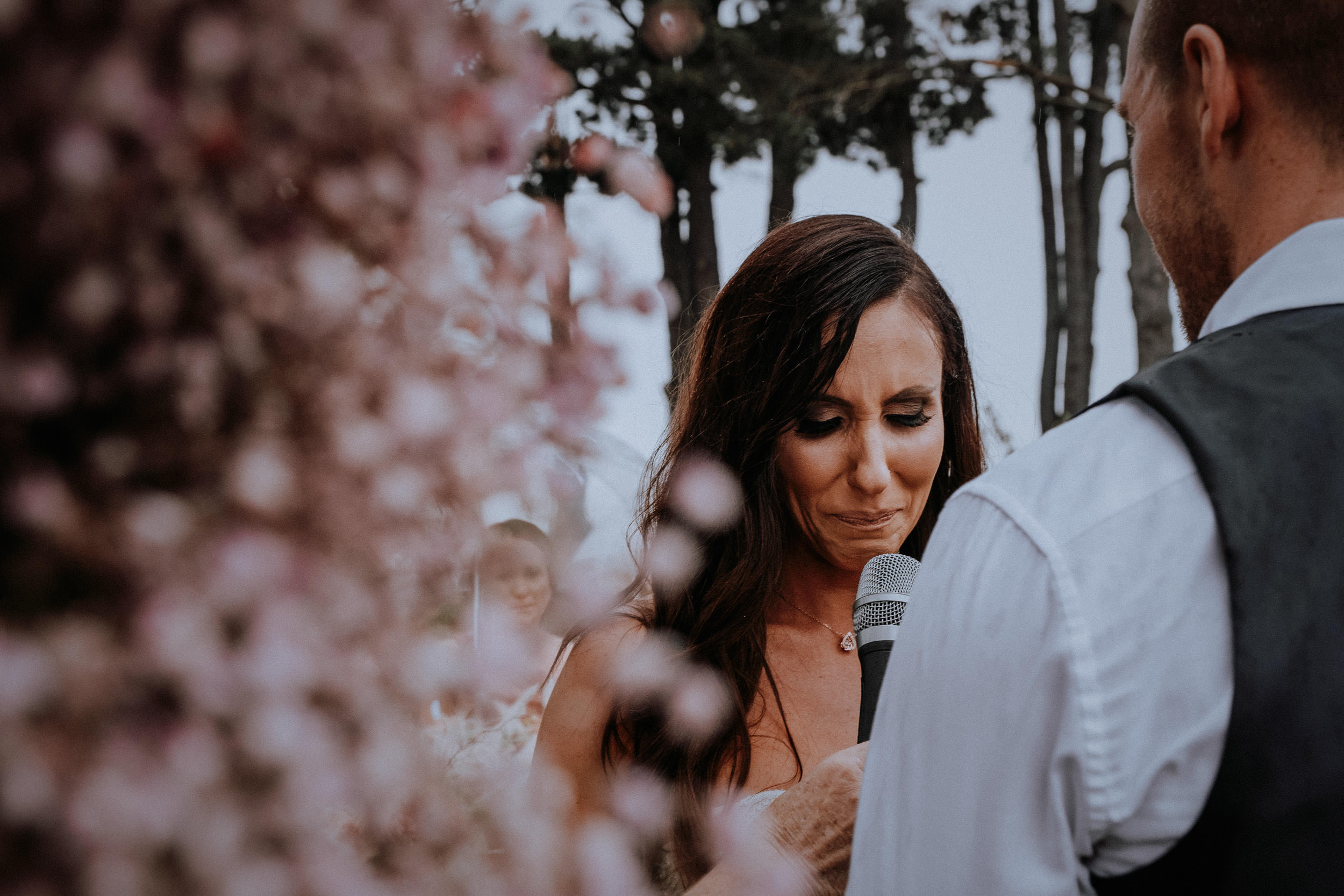 An emotional bride giving her vows to her groom during their wedding ceremony