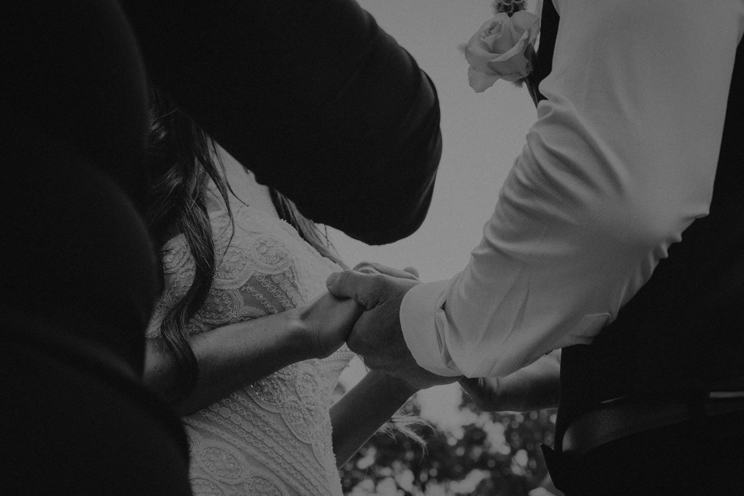 A black and white wedding photo of a bride and groom during their ceremony at Seclusions