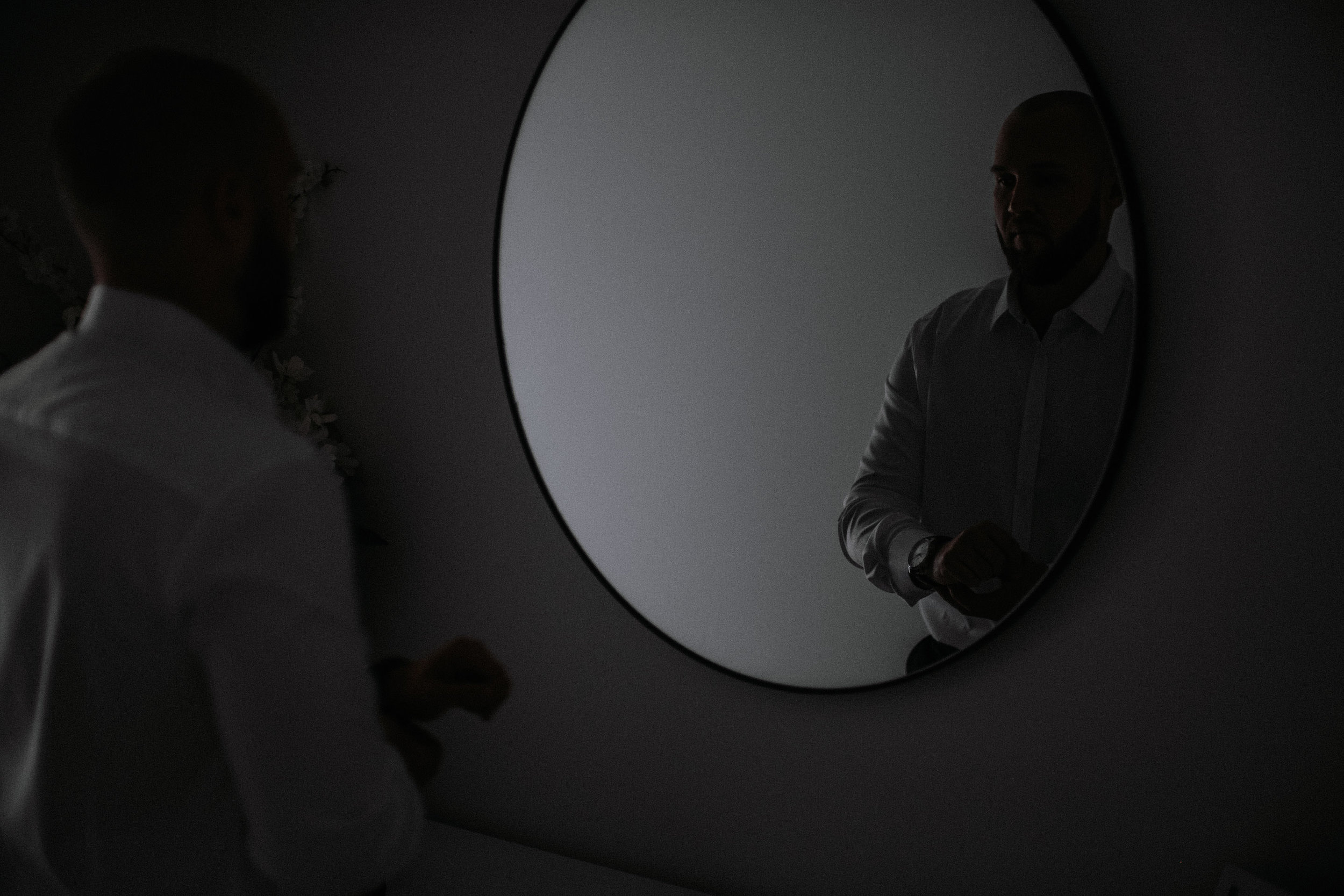 A groom getting ready in a mirror at his home before his wedding