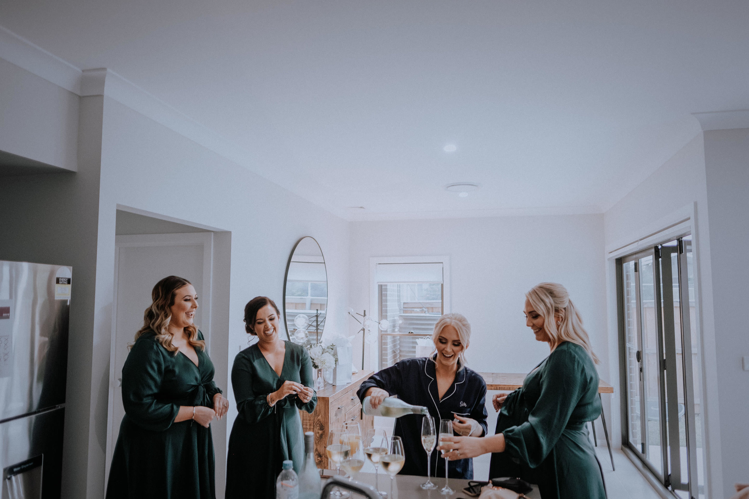 A bride and bridesmaids celebrating with champagne before the wedding