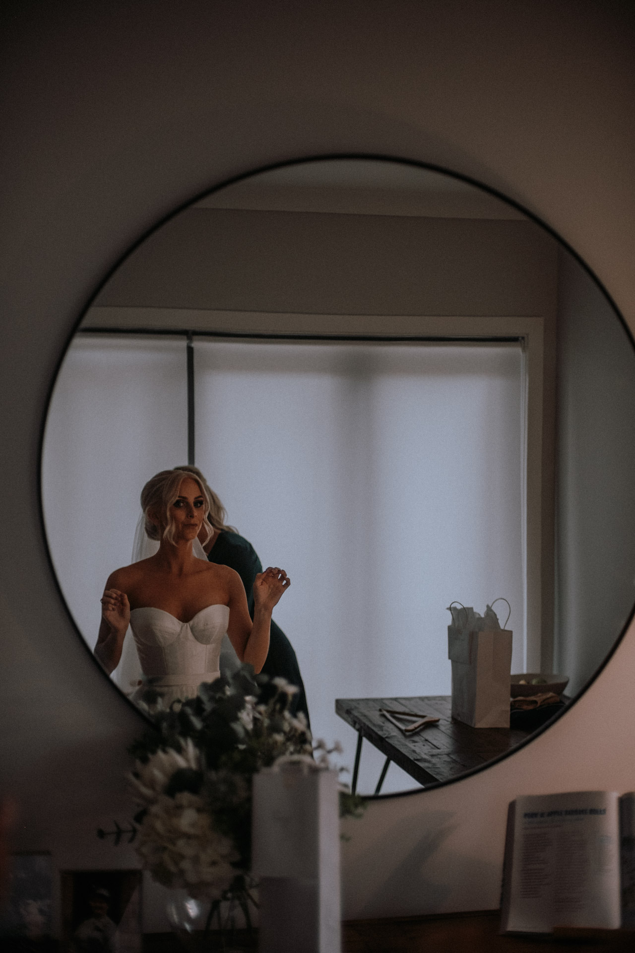 A bride having her veil fitted in the mirror