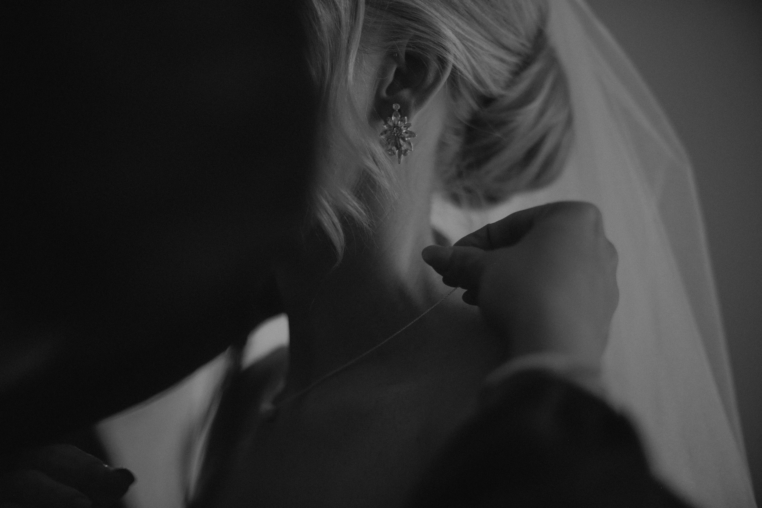 A bride putting on her necklace, a gift from her groom