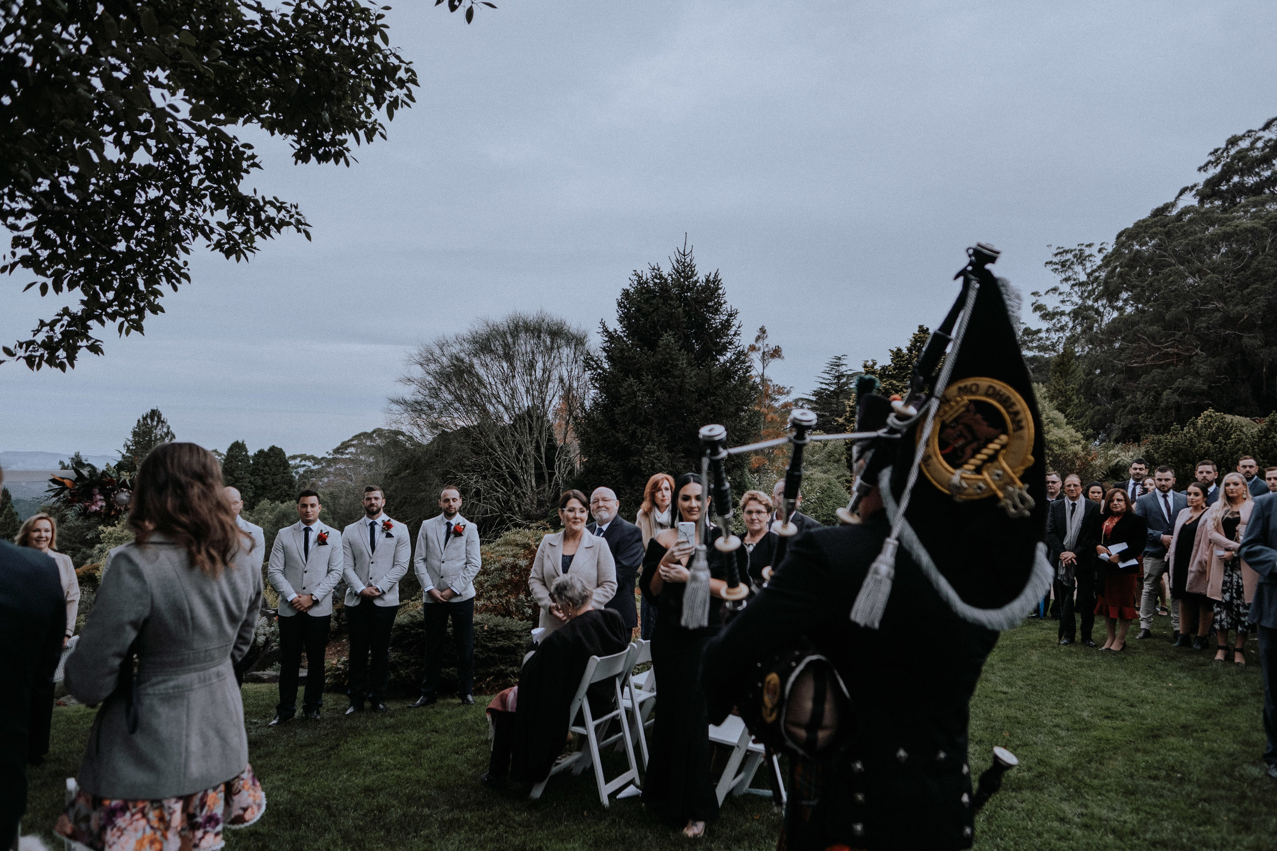 A bagpiper surprises guests at a winter wedding at Mt Tomah Botanic Gardens