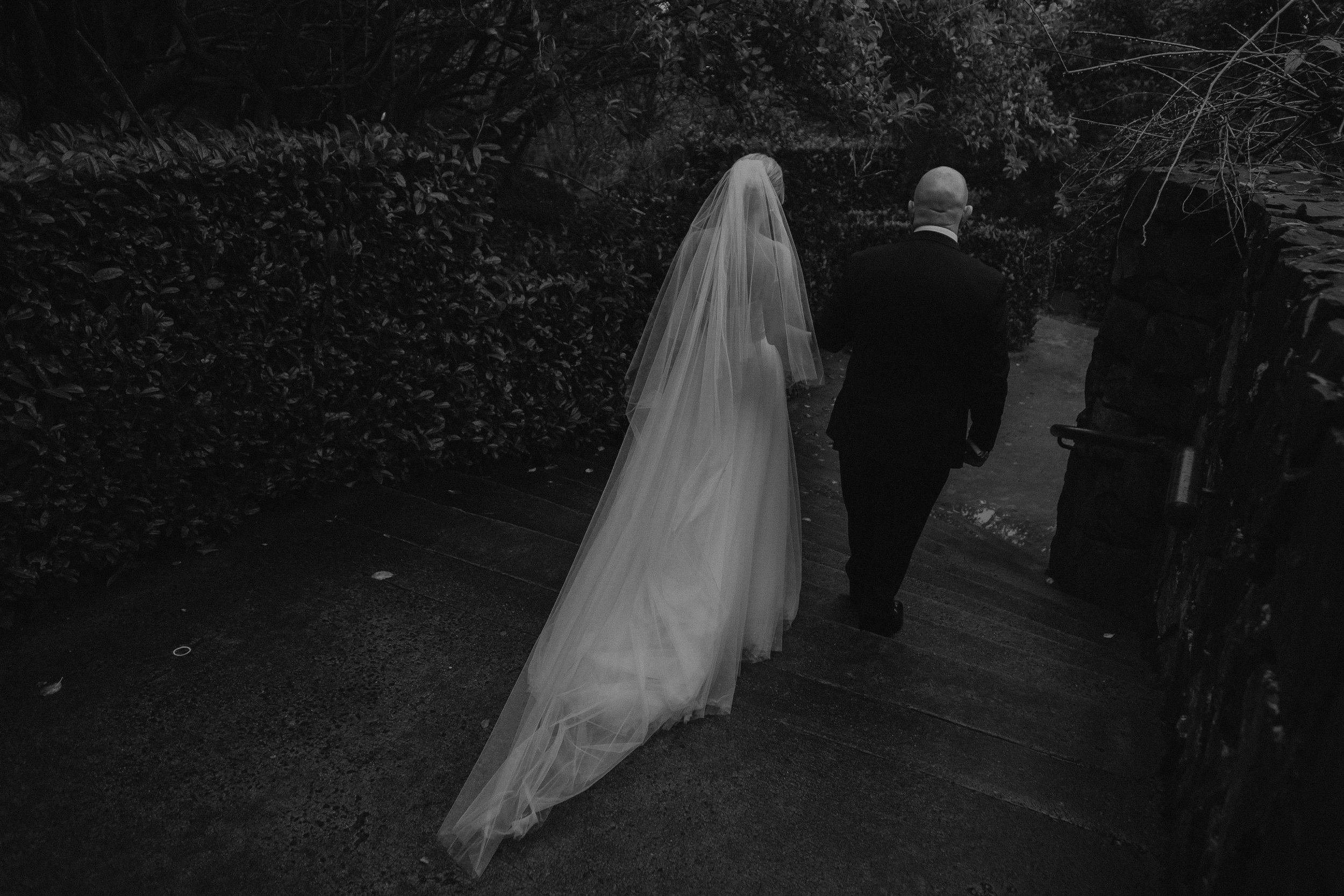 A bride walking down the grand steps with her father toward the aisle at her wedding at Mt Tomah Botanic Gardens
