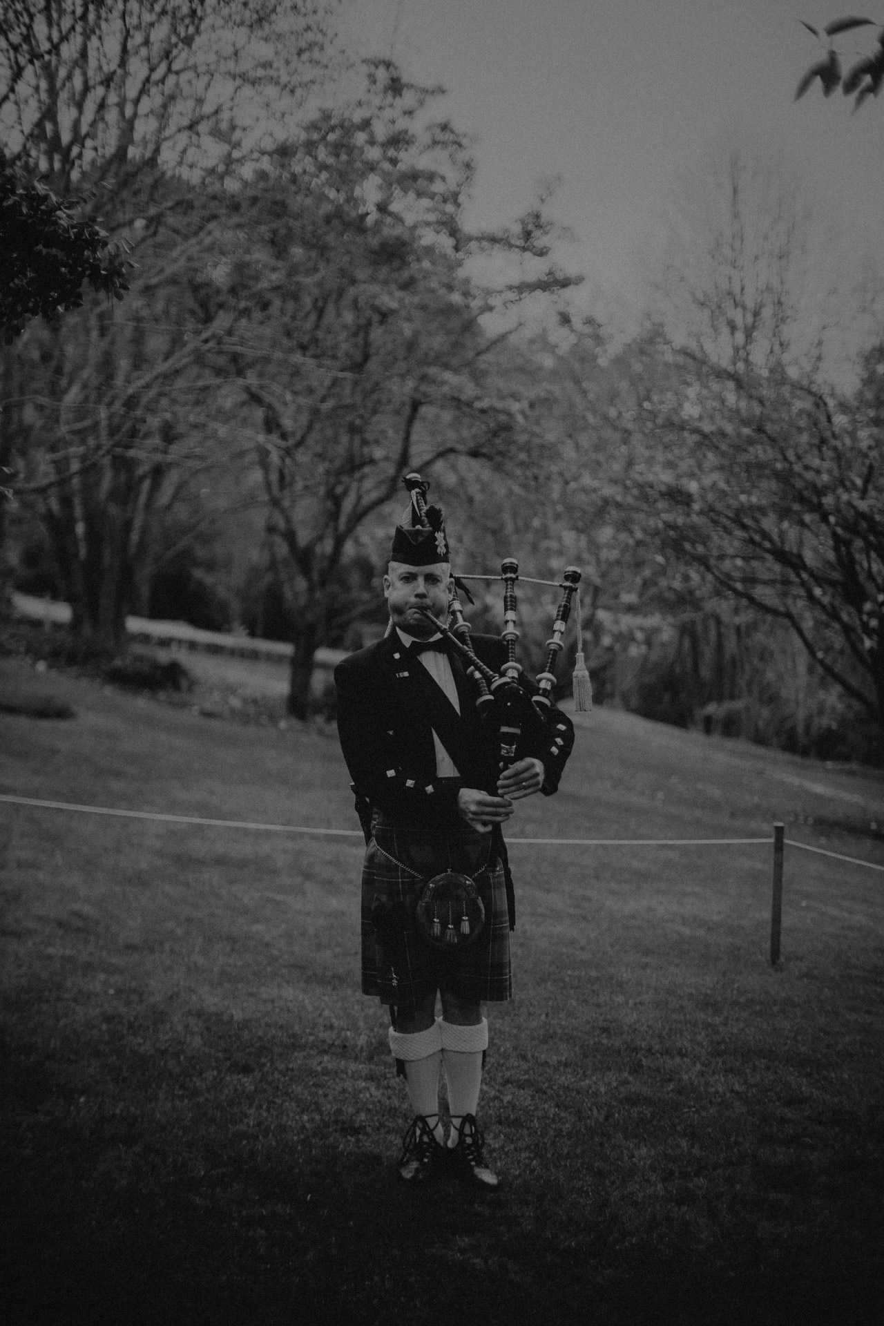 A bagpiper at an outdoor winter wedding ceremony at Mt Tomah Botanic Gardens