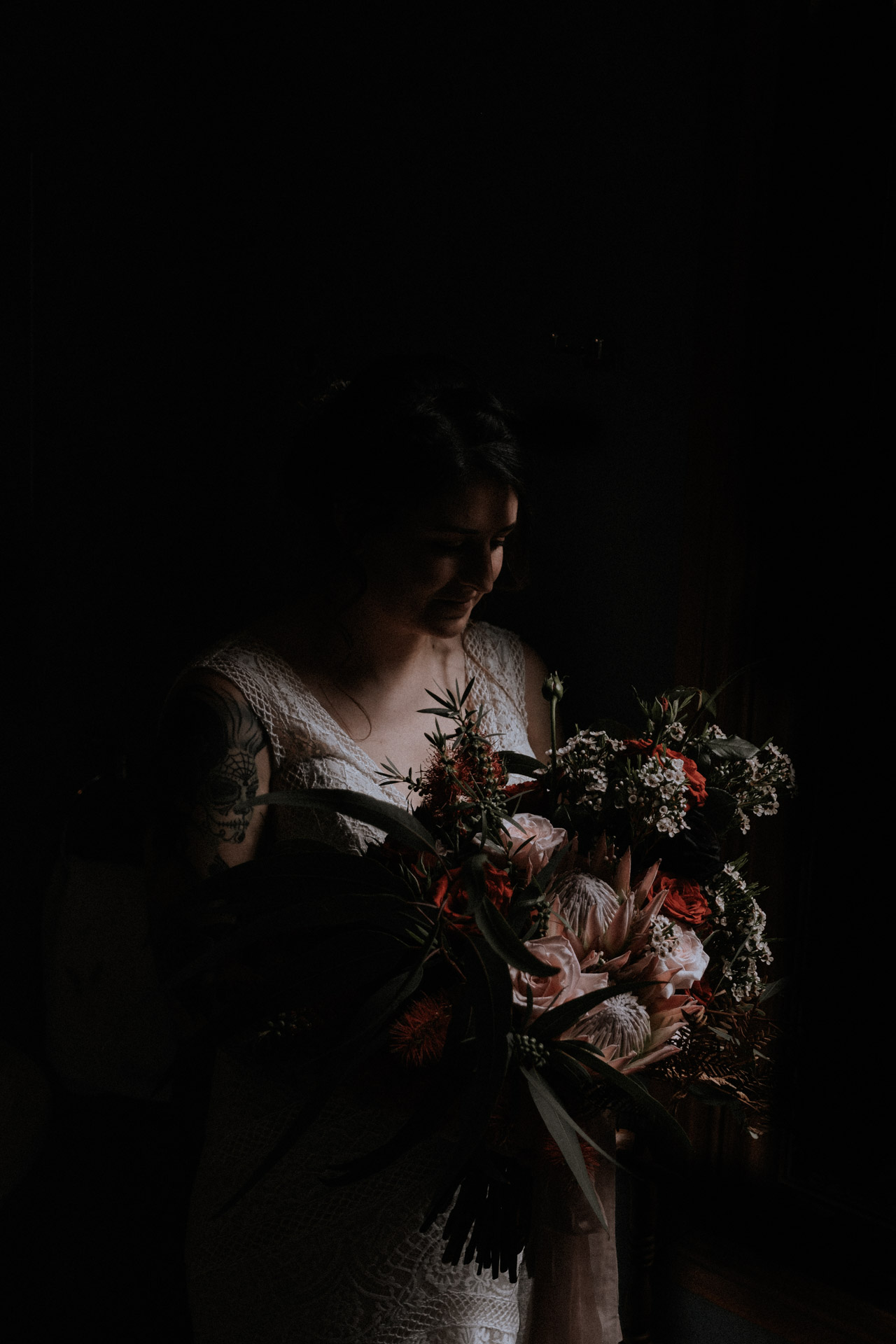 Window-lit portrait of a bride holding a bouquet before her small wedding at the Redwood Forest in Warburton, near Melbourne