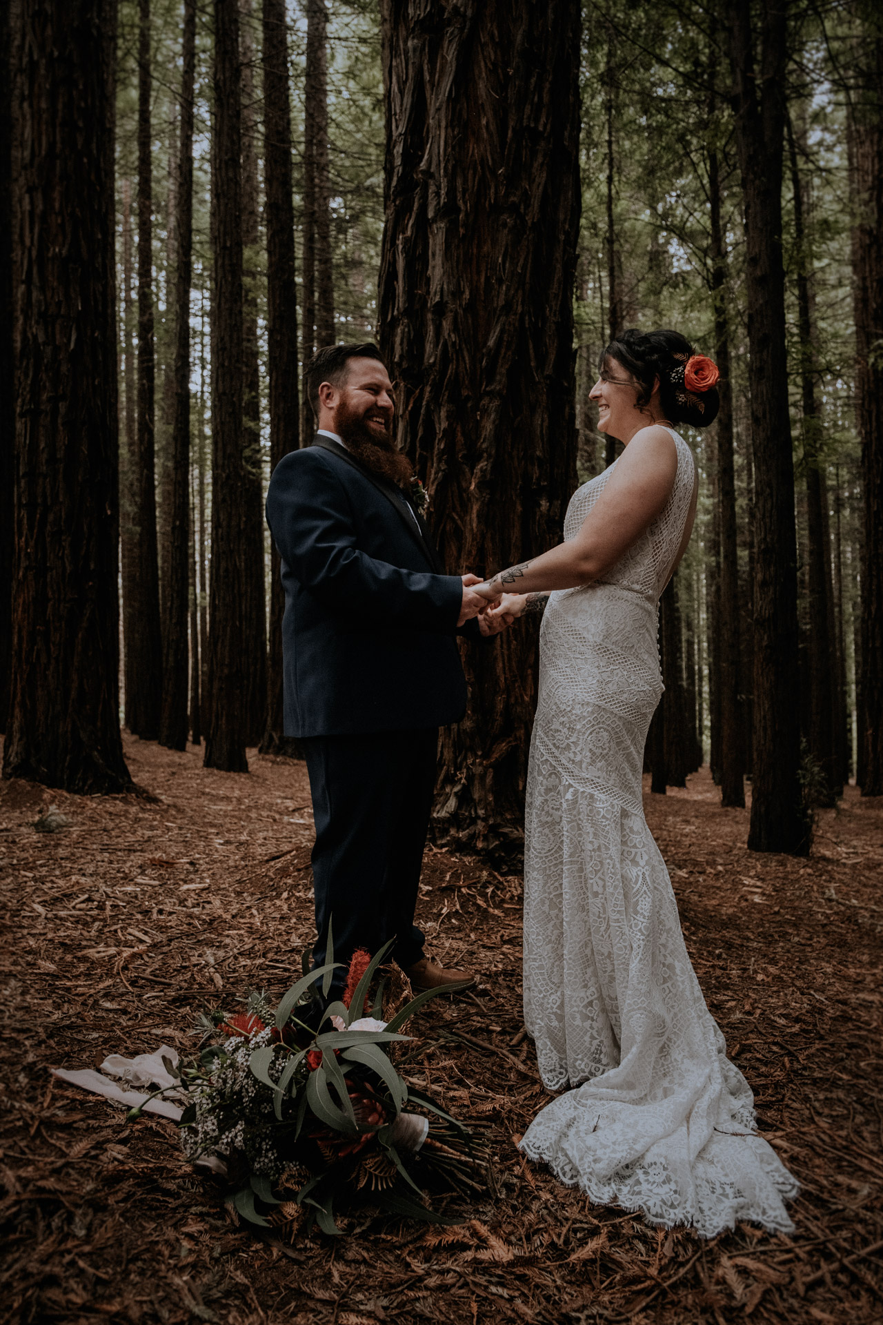 A bride and groom holding hands at their small wedding, candidly captured with intimate vibes, in the Redwood Forest in Warburton, near Melbourne