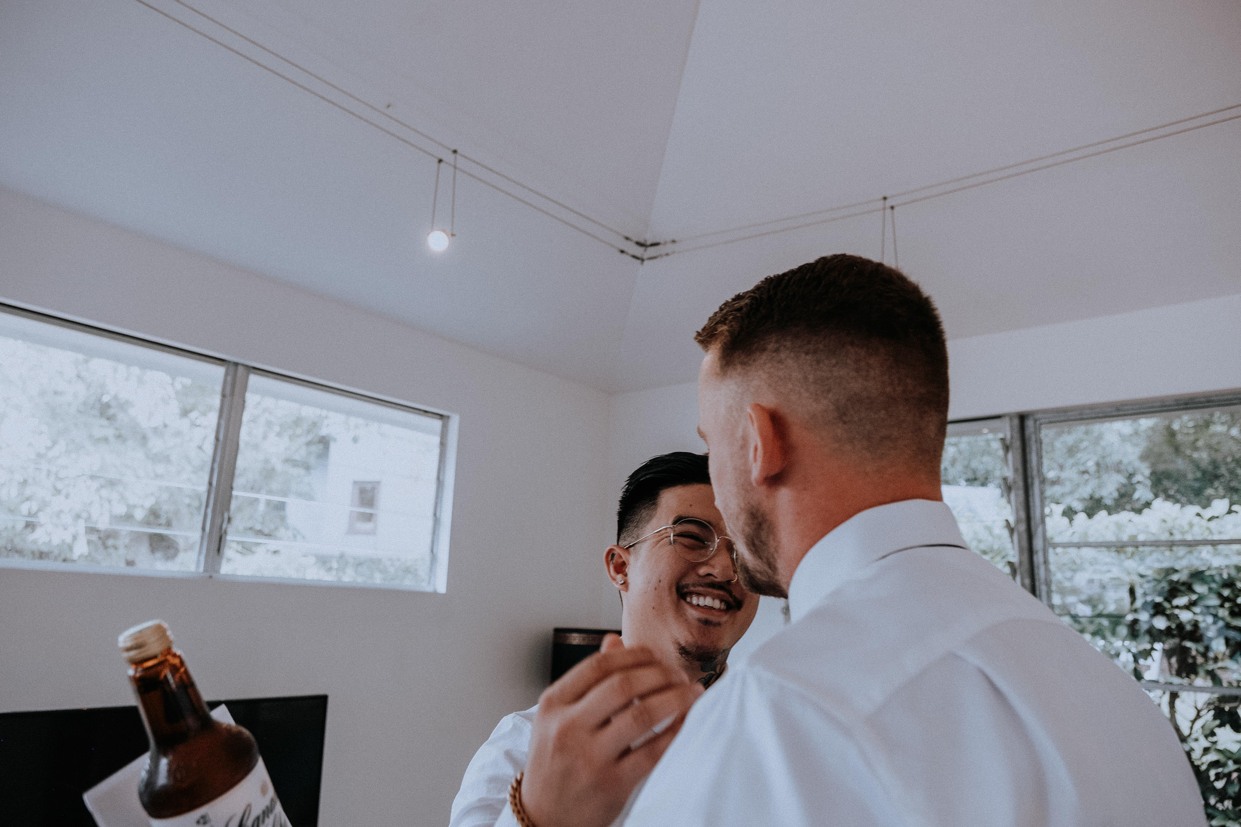 Groom and groomsmen having a laugh, sharing gifts and hugging