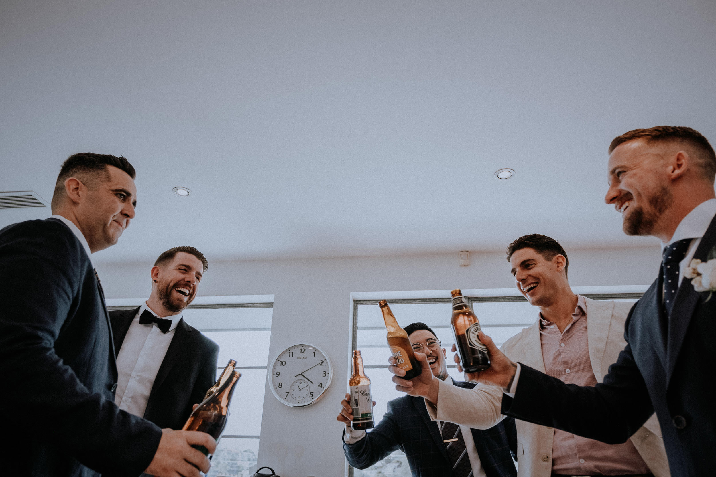 The wedding party celebrate with beers before heading down the aisle