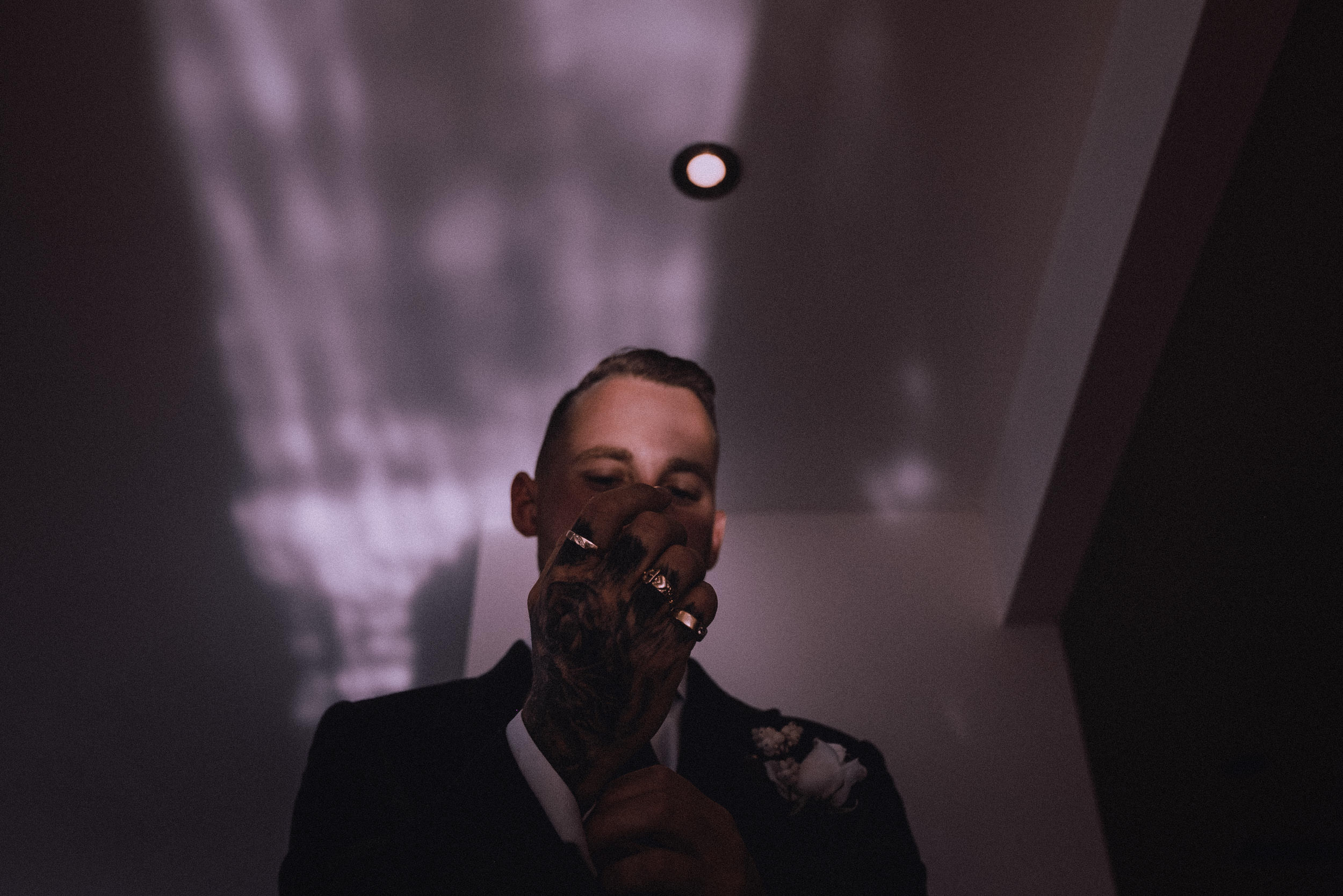 An artistic portrait of a groom preparing for his wedding