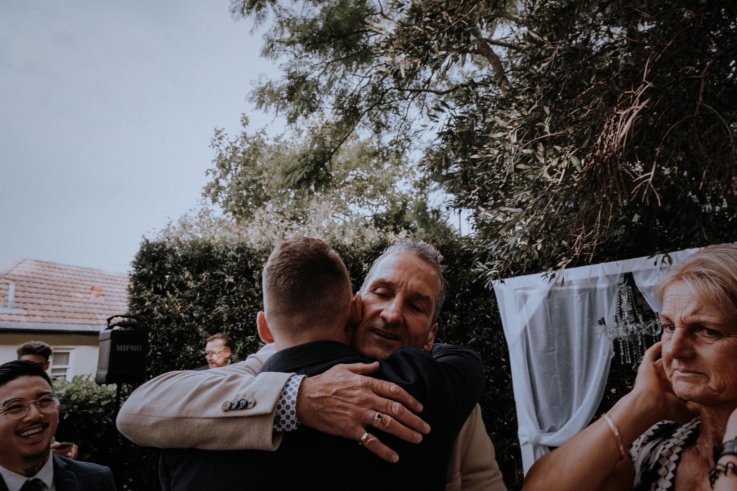 An emotional dad embraces his newly married son after his surprise wedding in Sydney