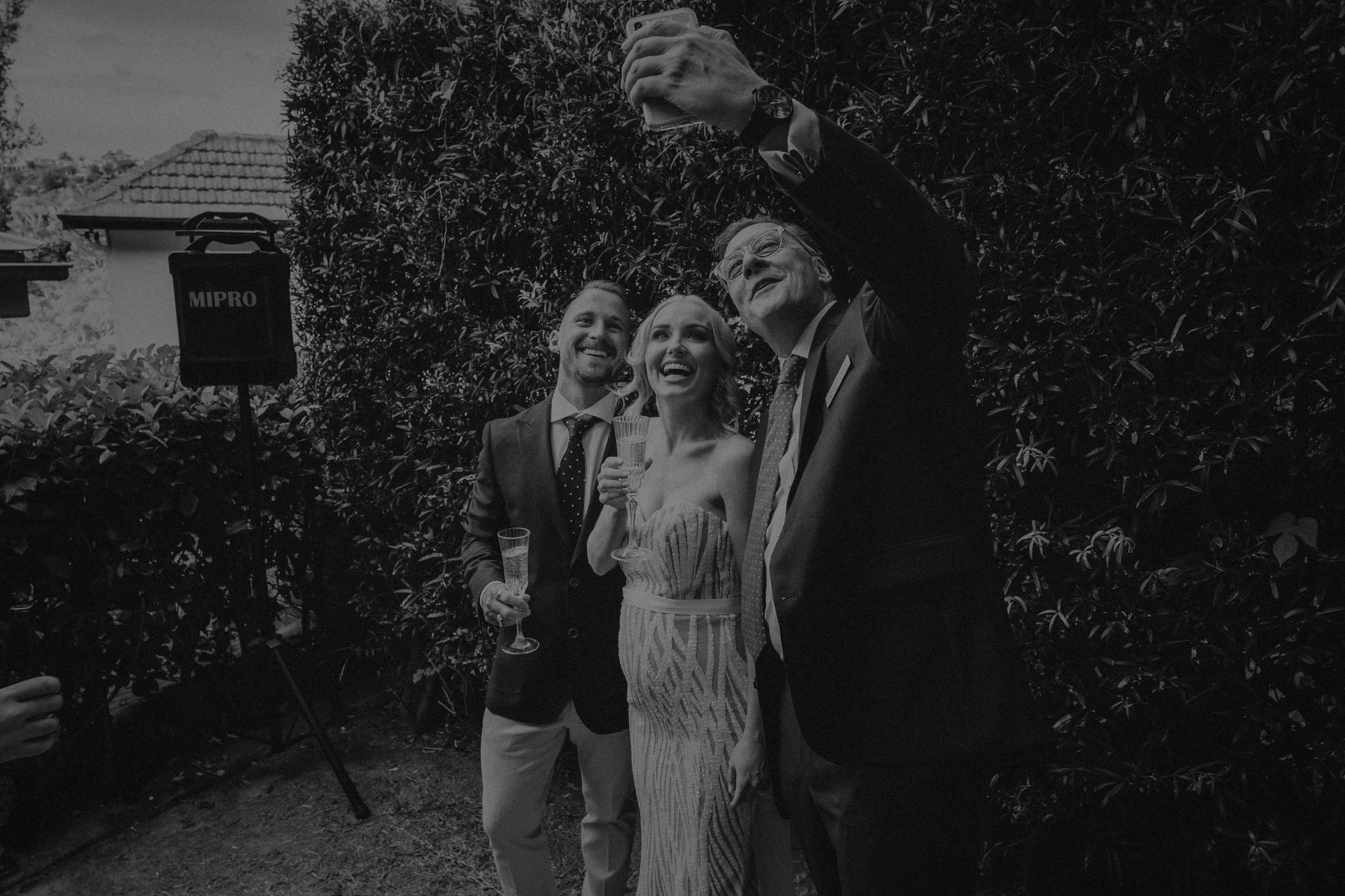 The wedding celebrant takes a selfie with the newly married husband and wife