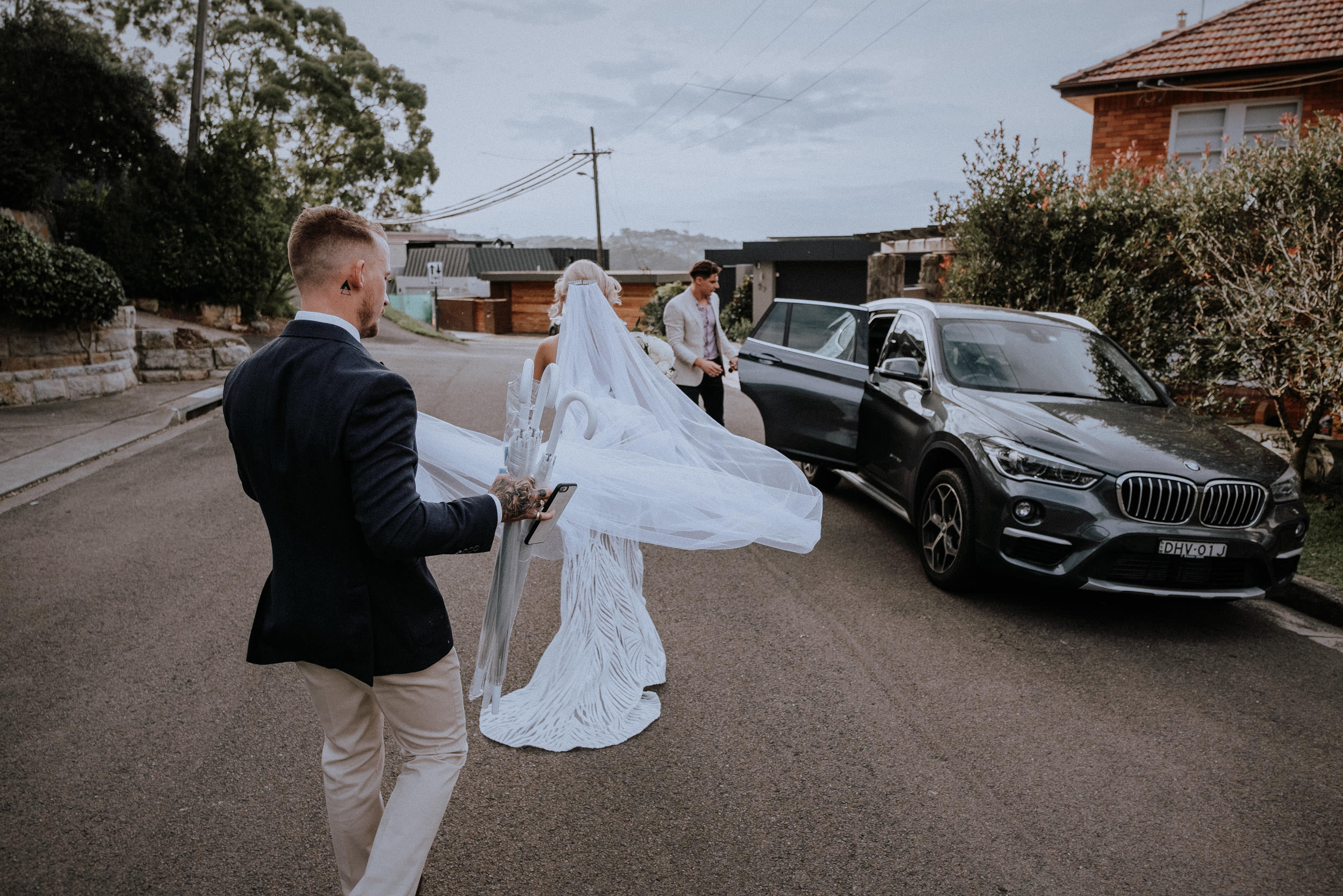 A bride and groom walking to the car to travel to Sydney Harbour for their sunset wedding photos