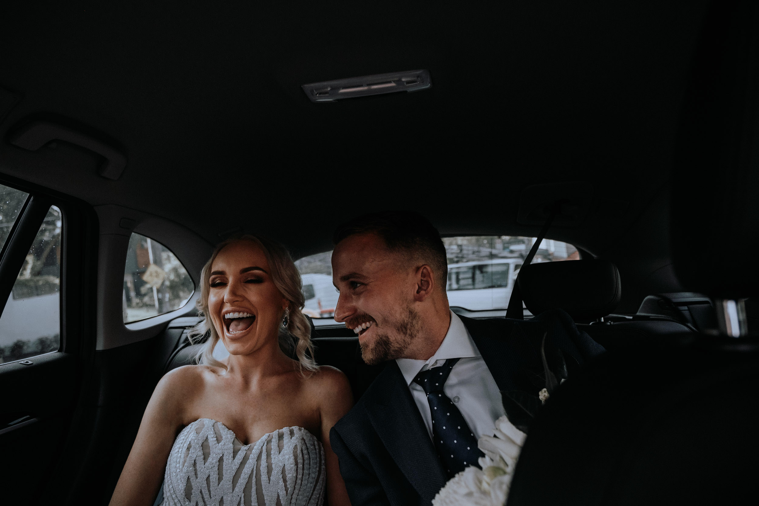 A bride and groom in the car travelling to Sydney Harbour for their sunset wedding photos