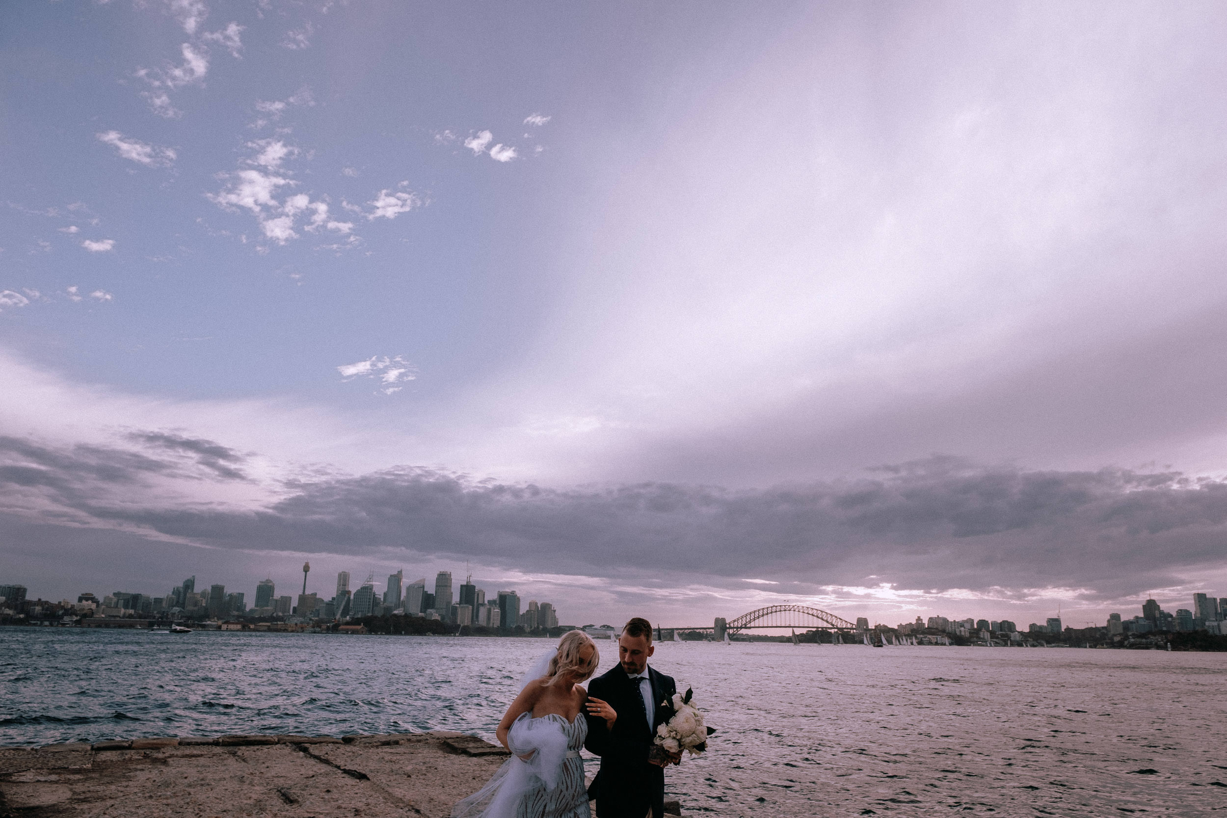 An epic frame of a newly married bride and groom at Bradley's Head, on Sydney Harbour, at sunset, with Sydney City, the world-famous Opera House and Harbour Bridge in the background