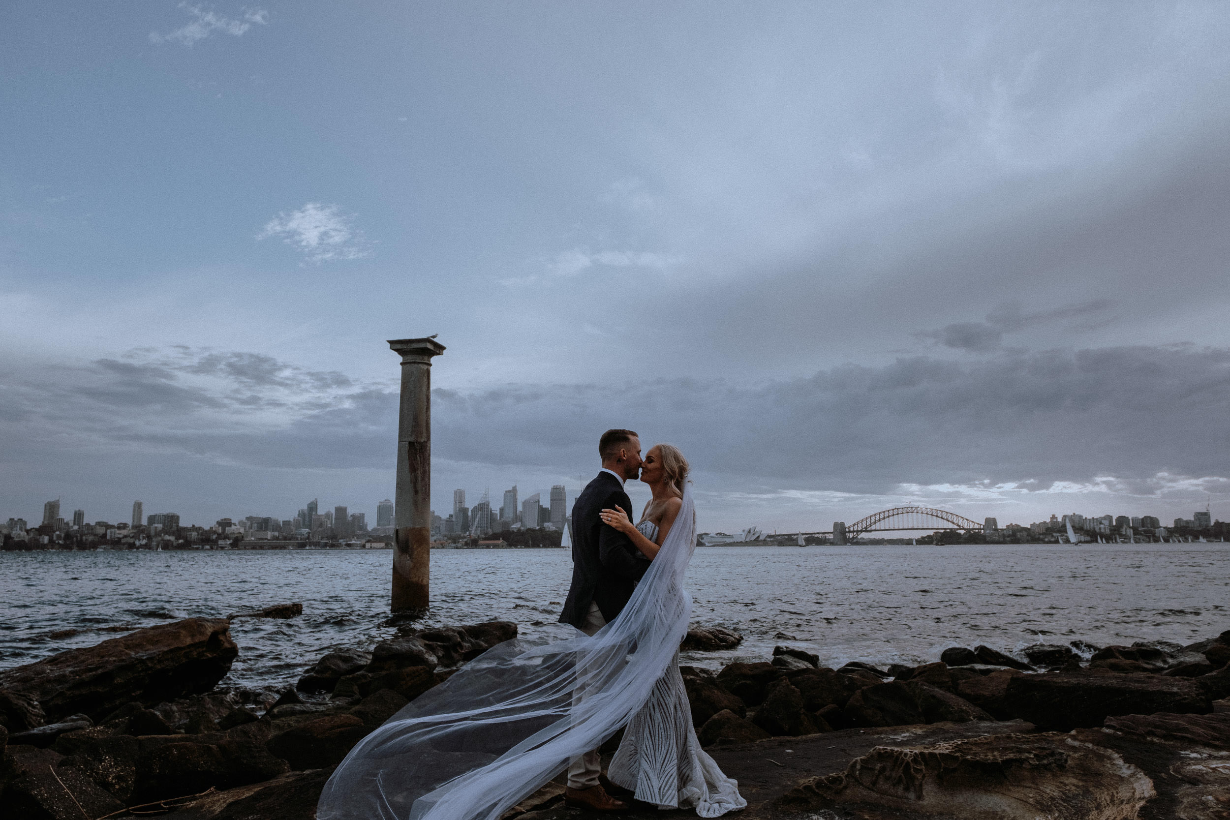 A powerful frame of a newly married bride and groom at Bradley's Head, on Sydney Harbour with Sydney City in the background, at sunset