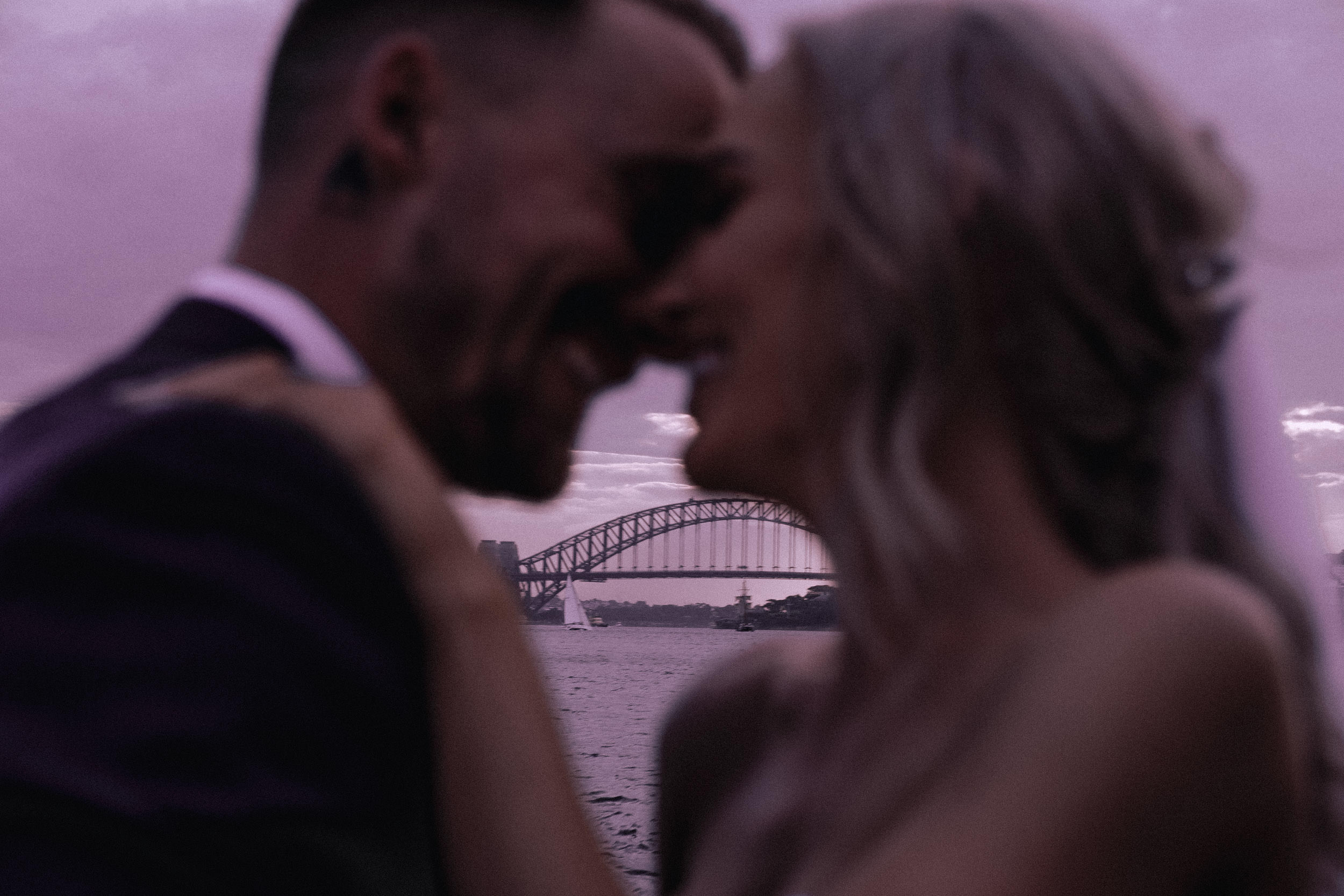 An intimate frame of a newly married bride and groom at Bradley's Head, on Sydney Harbour with the Sydney Harbour Bridge in the background, at sunset