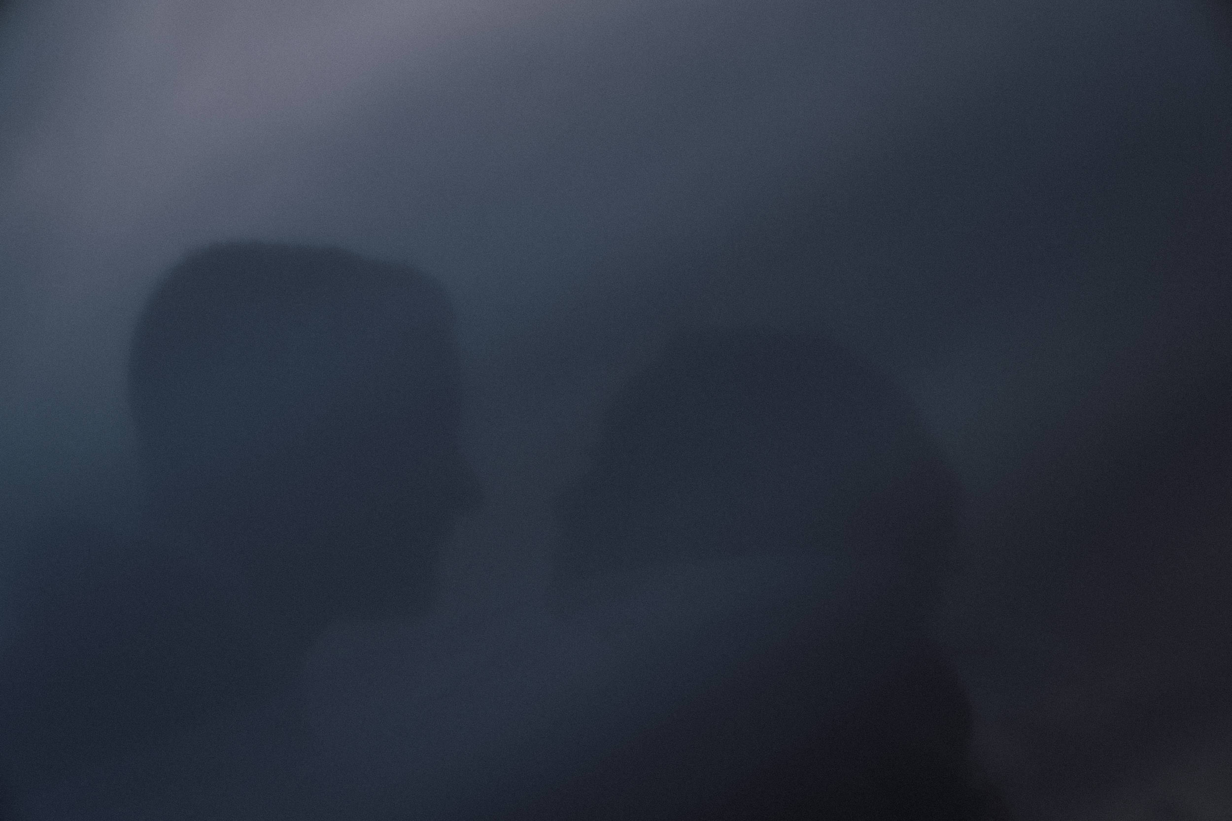 A silhouetted and intimate frame of a newly married bride and groom at Bradley's Head, on Sydney Harbour, at sunset