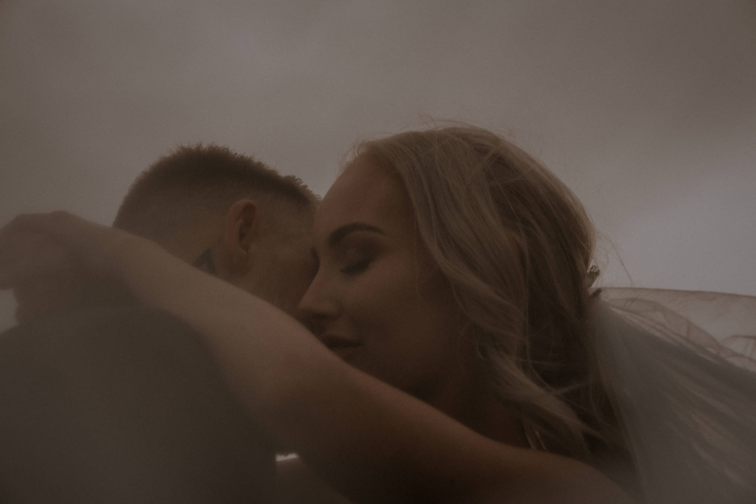 An intimate frame of a newly married bride and groom at Bradley's Head, on Sydney Harbour, at sunset