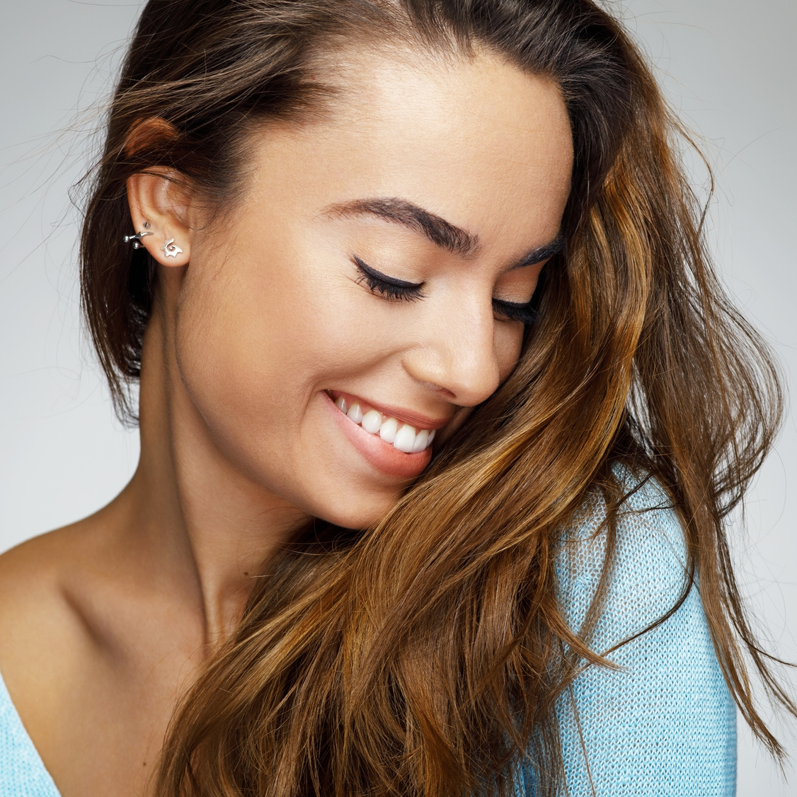 Young woman with white teeth smiling and looking down at her hair biddulph