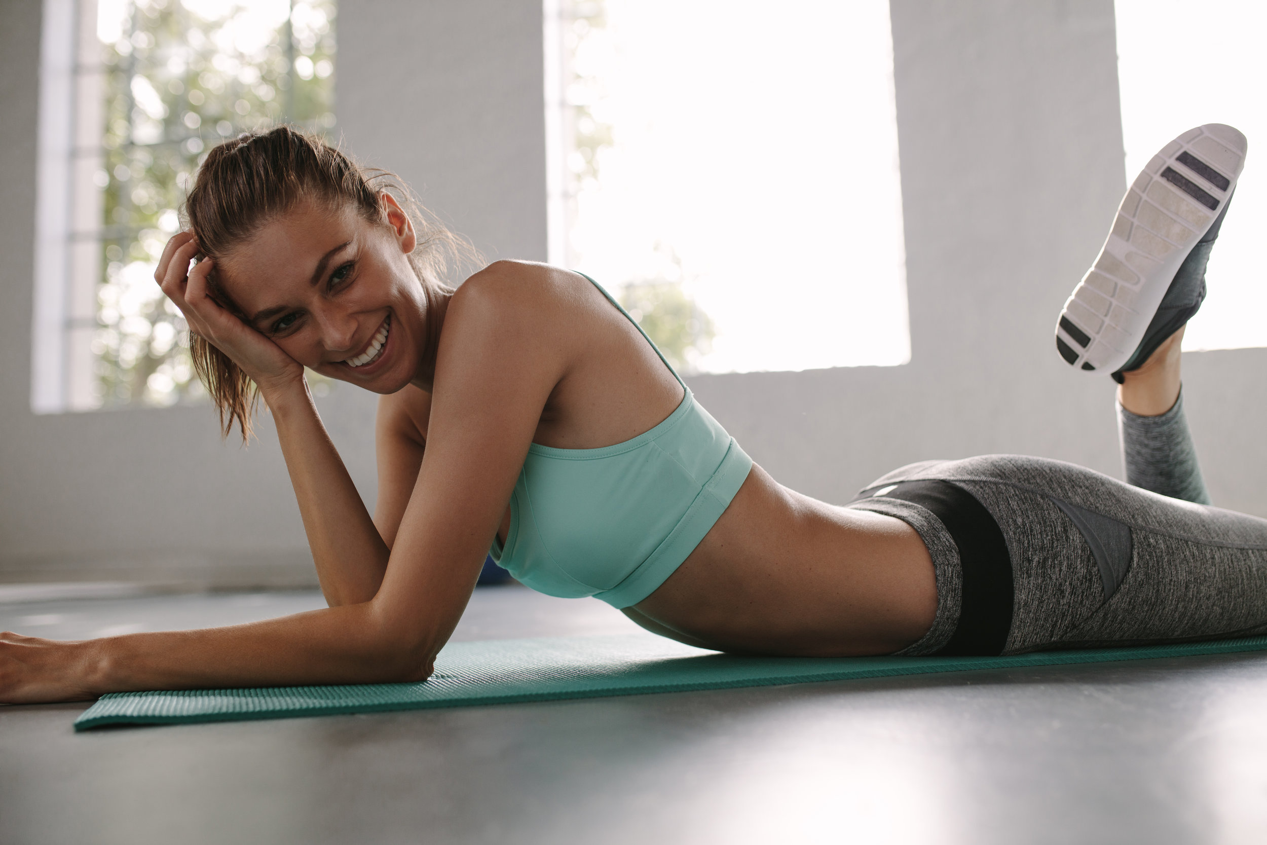 Fitness female lying on exercise mat in gym and smiling