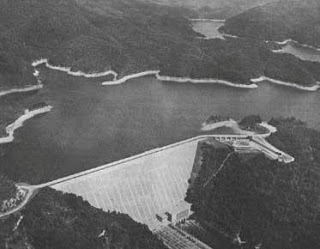 - This is an aerial view of the tallest dam in the eastern USA. Fontana Dam. 480 feet tall. It was constructed in the NC mountains in Welch Cove during World War II in only 3 years! Notice the tiny building at the base of the dam? That building is 7 stories tall. Huge Fontana Lake was created when water from a river backed up behind the dam and flooded over 7,000 acres, including 7 former towns. ALCOA plants needed electricity produced at the dam to run their aluminum plants - aluminum for war machinery.