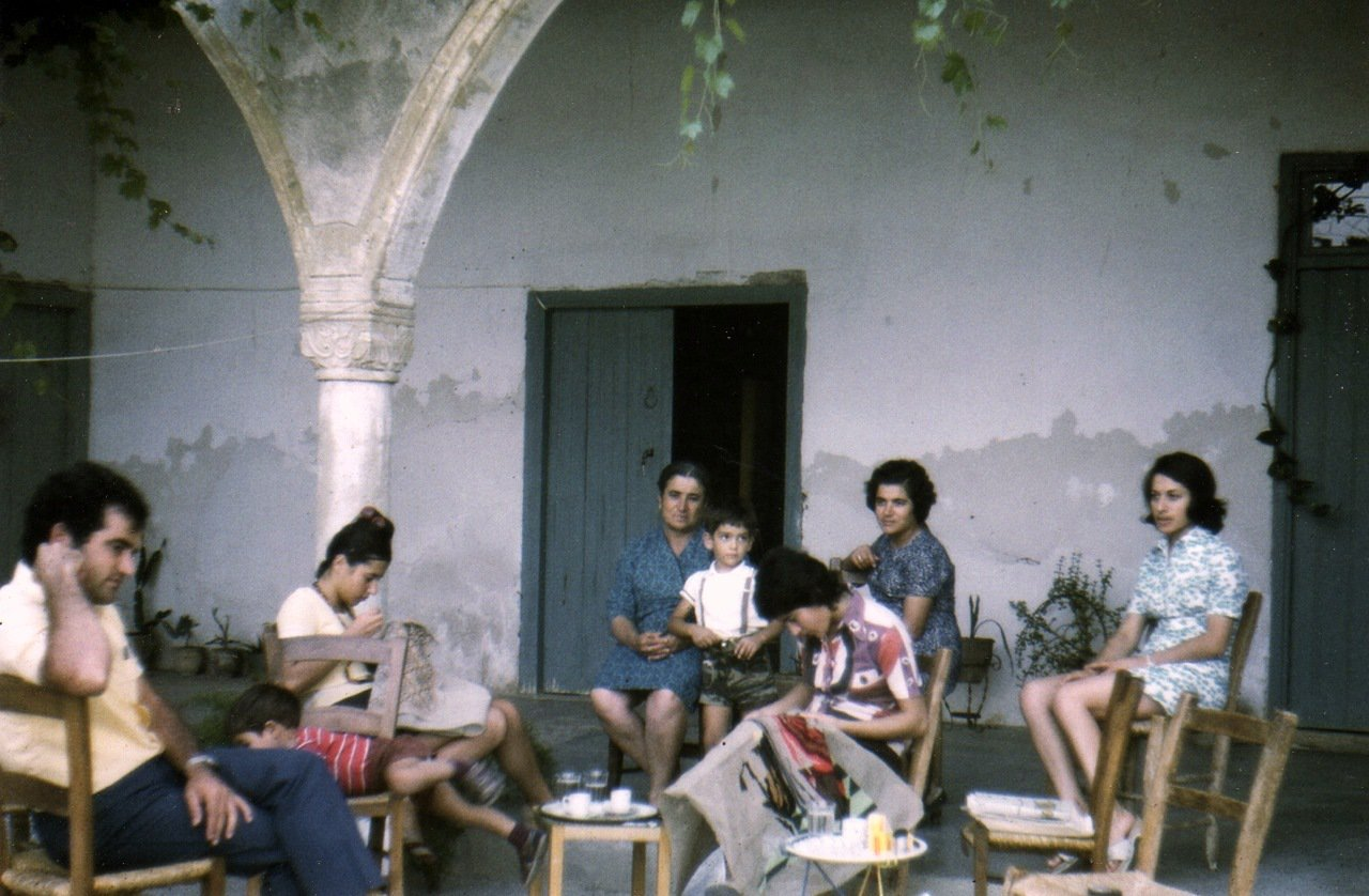 Photograph of my grandmother, my mother, my three aunts, my uncle and two of my cousins in the early 70s sitting outside their front door in their village Gerolakkos.
