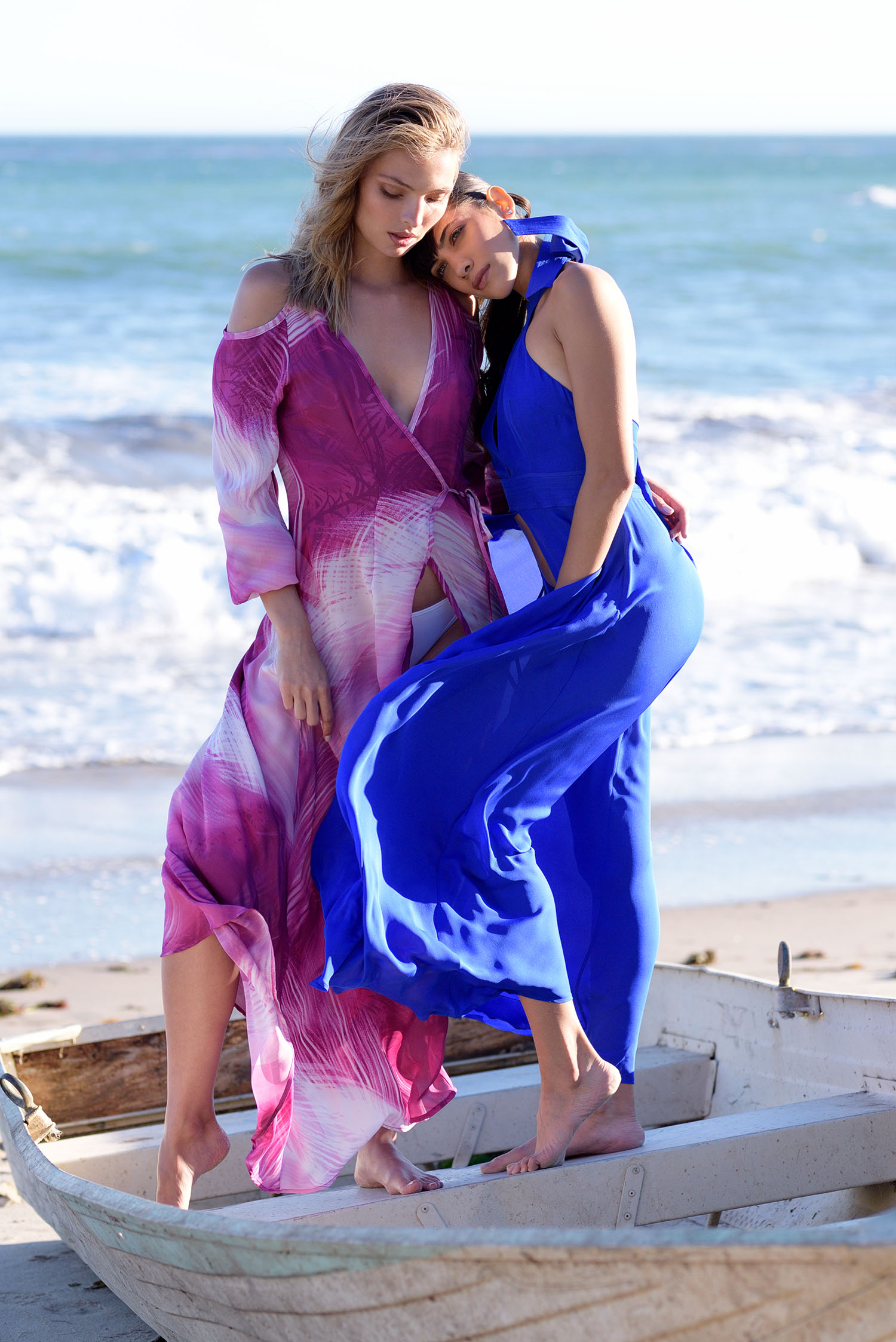 Carola Remer and Liz Mittra are stranded on a boat washed ashore in elegant gowns blowing in the ocean breeze for resort wear campaign