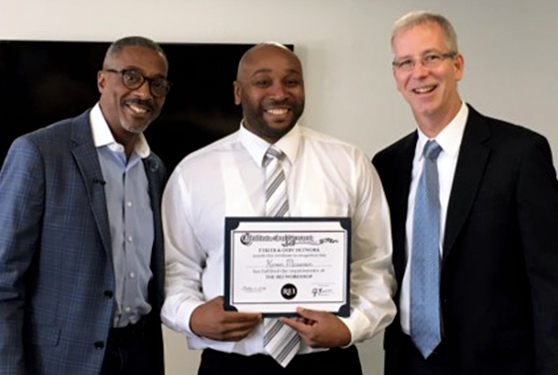 Tracey Syphax and C.J. Meenan present a reentry student with a program certificate.