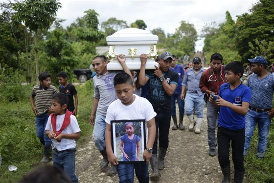 A boy carries a picture Jakelin Caal while her coffin is carried to the cemetery in San Antonio Secortez, Guatemala, on Dec. 25, 2018.Johan Ordonez / AFP - Getty Images