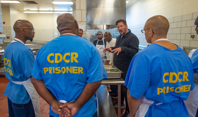 Huw Thornton, center, leads a groups of inmates in while working in the kitchen of H-unit at the California State Prison in San Quentin, Calif. Tuesday, May 14, 2019. (Jeremy Portje/ Marin Independent Journal)