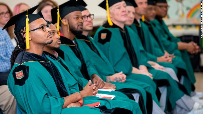 Larry Marshall (left) and fellow graduates sit at their commencement. They received Associate of Arts degrees from Washington University in St. Louis through the school's Prison Education Project.