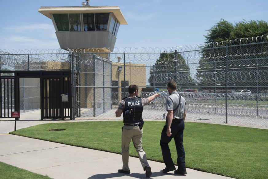 A police officer and a correctional officer patrol the entrance of the El Reno Federal Correctional Institution in El Reno, Oklahoma.SAUL LOEB/AFP, VIA GETTY IMAGES