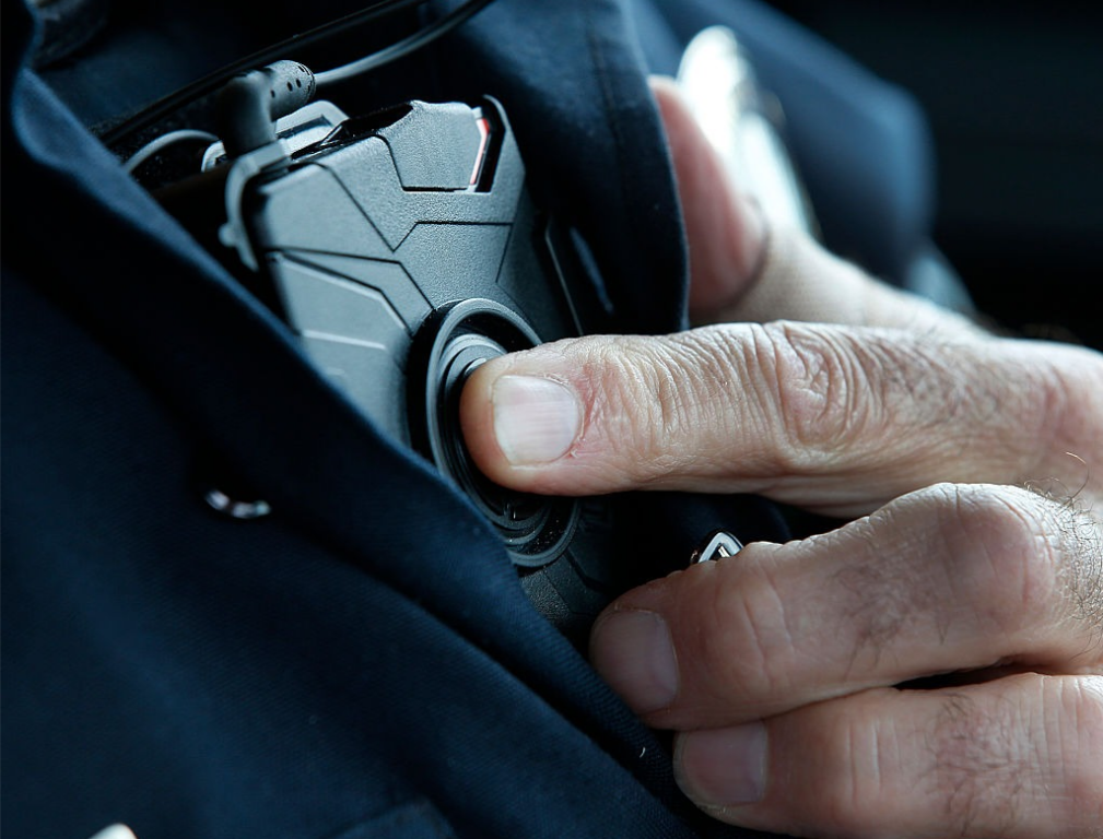 A patrol officer with the West Valley City, Utah Police Department starts a body camera recording by pressing a button on his chest before he takes a theft report from a construction on March 2, 2015. The West Valley City Police Department has issued 190 Taser Axon Flex body cameras for its sworn officers. Photo by George Frey/Getty Images