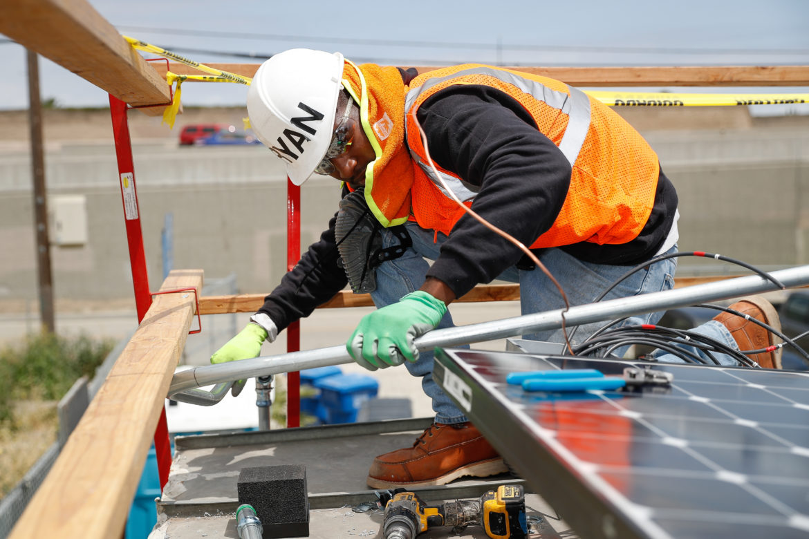 Ryan Shelton of Grid Alternatives fits a pipe during a solar installation in Los Angeles, California. Shelton, 23, discovered Grid Alternatives' SolarCorps fellowship program shortly after his release from prison and is now working toward an associate degree and certificate in electrical construction and maintenance from a technical trade college in Los Angeles.