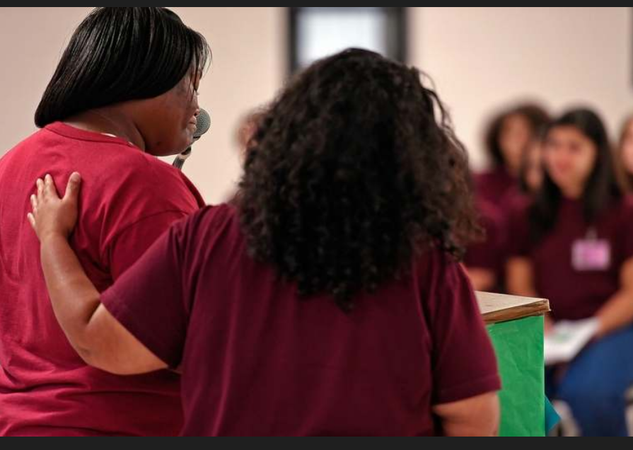 Robin Ledbetter, left, is comforted by fellow mentor Elizabeth Ruiz on Friday, June 21, 2019, as she offers her final reflection to fellow inmates and state and correctional officials during a one-year anniversary celebration of the WORTH, or Women Overcoming Recidivism Through Hard Work, unite at York Correctional Institution in Niantic. The program connects older inmates as mentors for younger inmates to help with their rehabilitation and reintegration. (Sean D. Elliot/The Day)
