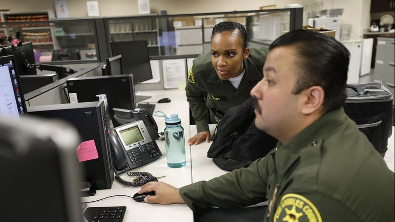 L.A. County Sheriff's custody assistants Alexis Herbert, left, and Victor Gamont screen requests from ICE to take custody of inmates. (Al Seib / Los Angeles Times)