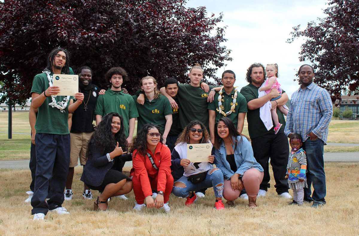Graduates of the Northwest Credible Messenger Green Hill School pilot program, in green polos, proudly celebrate with the program's mentors after the ceremony on Friday, June 21. Olivia Sullivan/staff photo