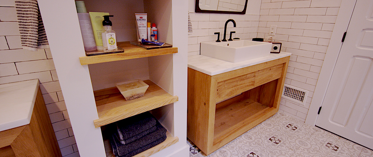 Simply Stylish - This vessel sink atop a custom wooden vanity makes a trend instantly timeless. Open shelving creates a perfect divider between his-and-her sink areas that make getting ready in the morning a breeze. The overall look is simple, clean, and classic.