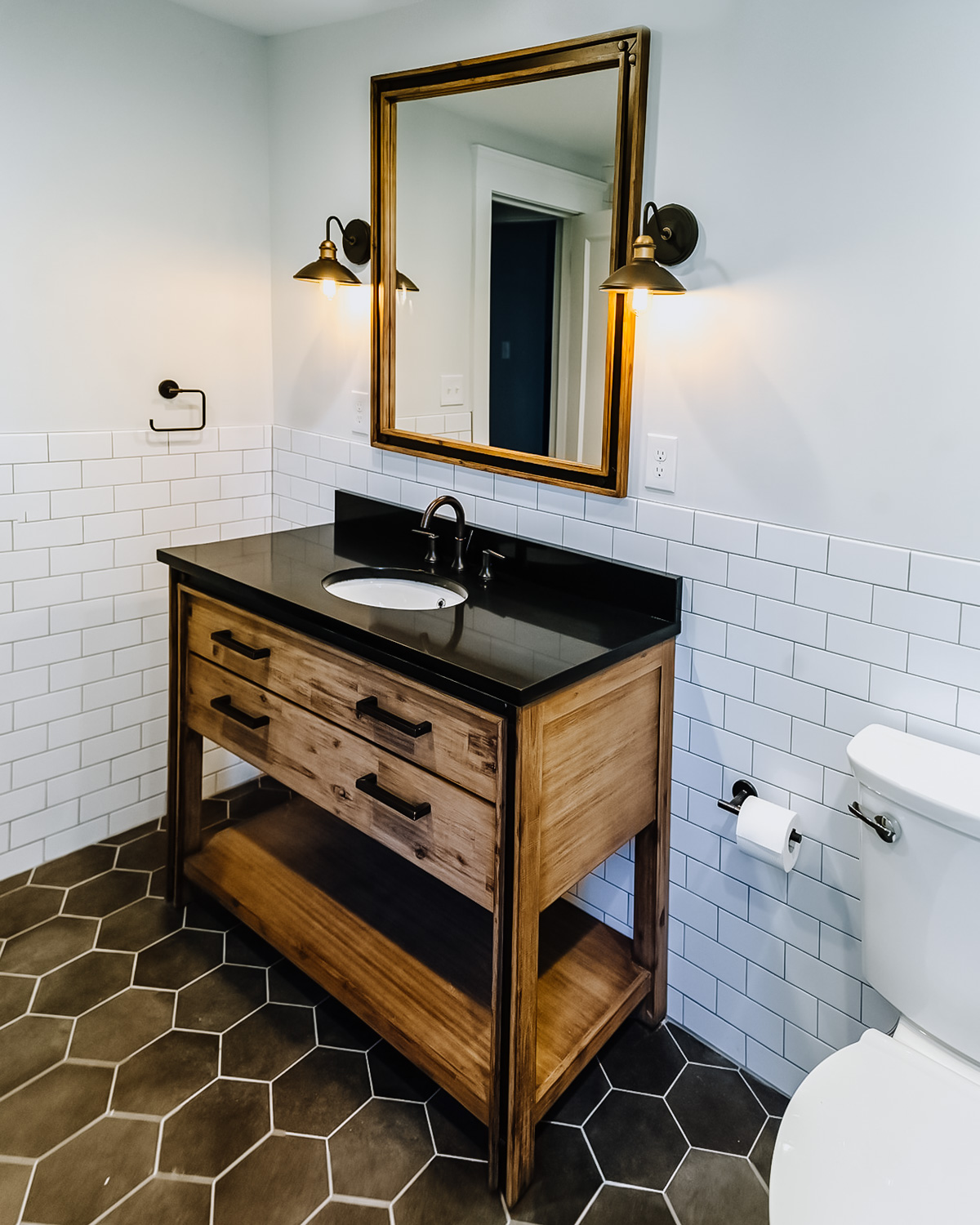 - Instead of a color play, this bathroom uses shapes to make a statement. We love the contrast of black and white, and rectangle and hexagon, of the wall and floor tile, giving a lovely palette for the natural wood vanity with black granite countertop, and ready for any accessories that homeowner might like to add to either add a pop of color or to layer on to these complex neutrals.