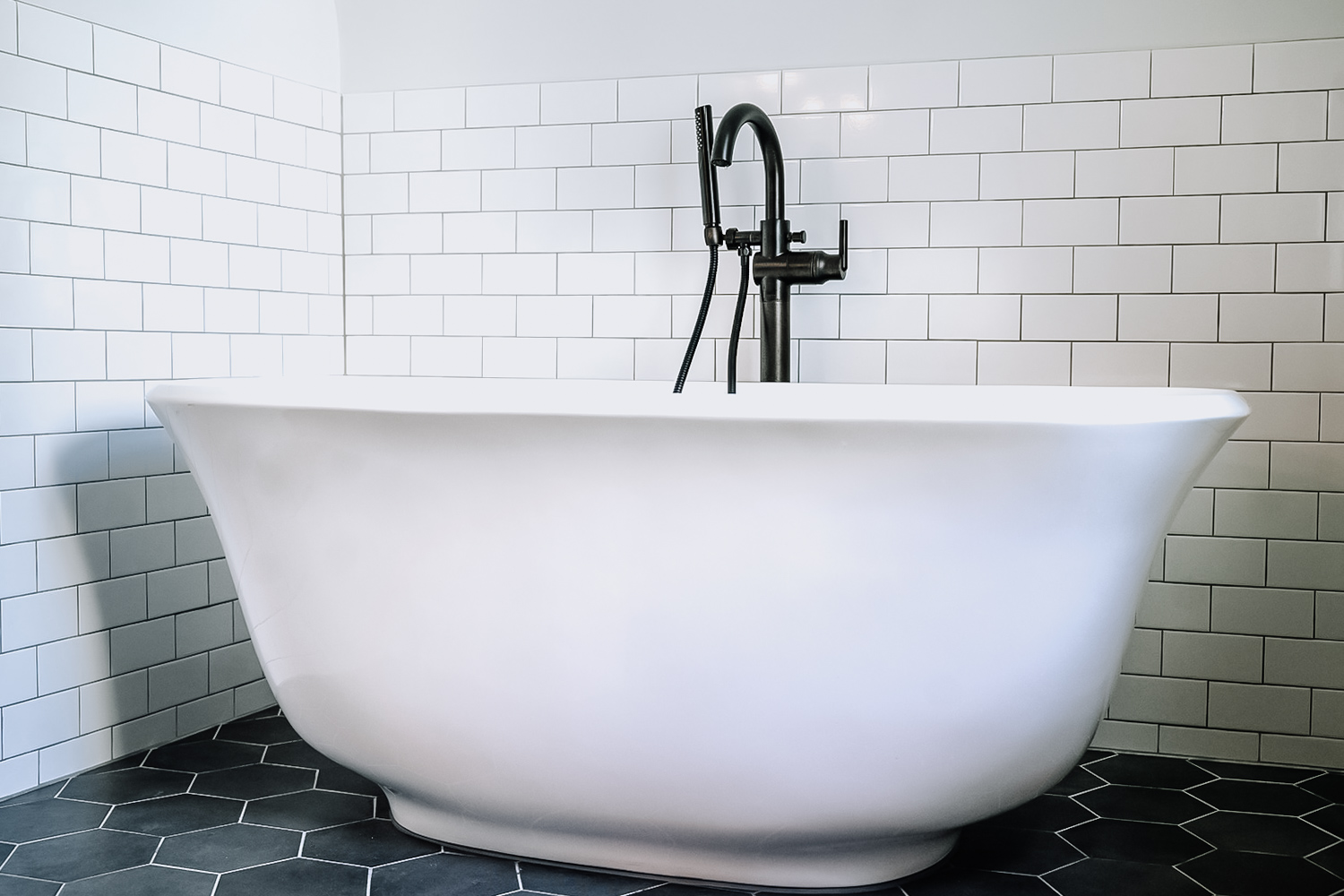 - Just when you thought this renovated bathroom could not get any more spa-like. This hall bathroom was remodeled to include the most perfect spot for a stand-alone tub. The curved shape of the bath tub adds a nice contrast to the geometric angles of the floor and wall tile.