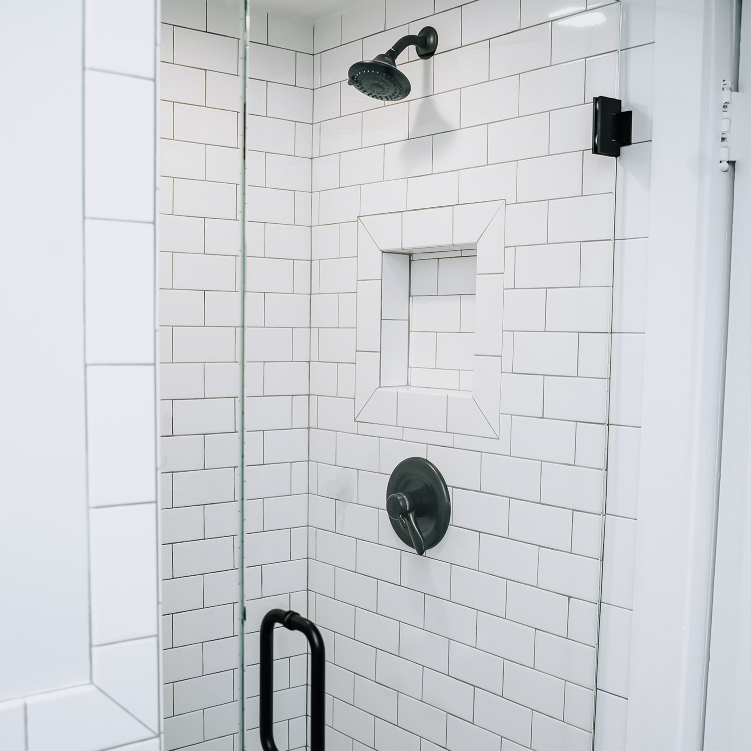 - The frameless glass shower doors add to the elegance of this space, where the hexagon floor tile makes another appearance, this time in a smaller scale. The tiled recessed shelf is artfully framed out, creating stylish shower storage. The Venetian Bronze fixtures lend an air of elegance.