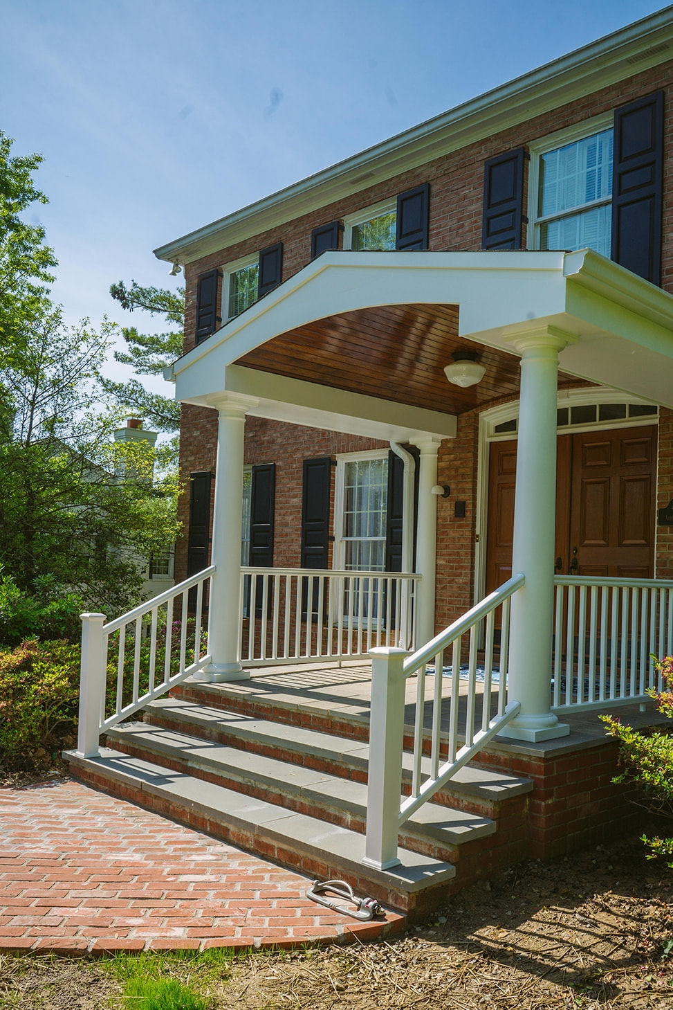 Welcome Home - First impressions are everything. And this new porch adds a stately entryway to this classic brick home. The slate covered flooring is both elegant and durable, creating quite a welcome for these proud homeowners.