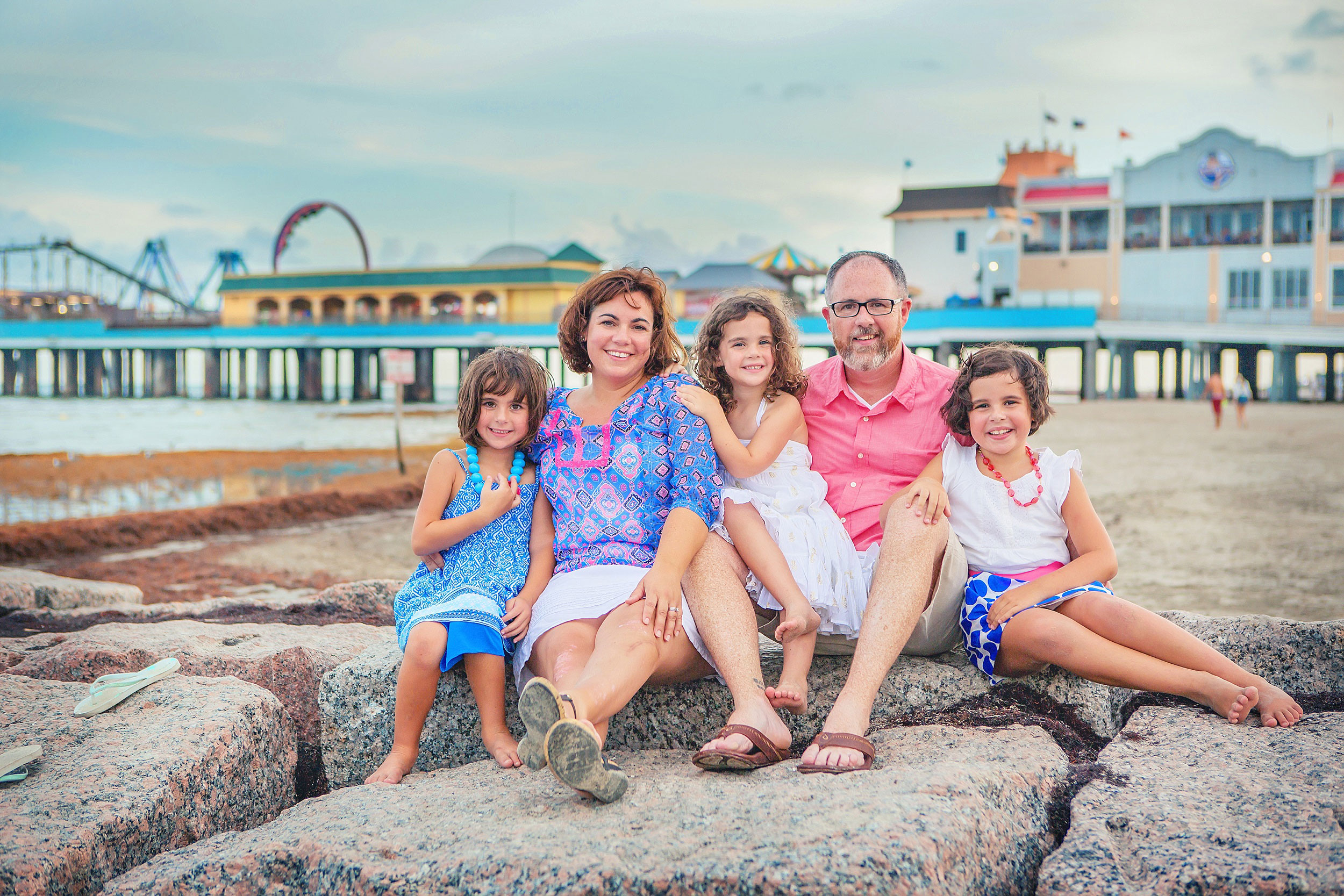 Family dressed in colorful clothes on the beach in Galveston by spryART photography.