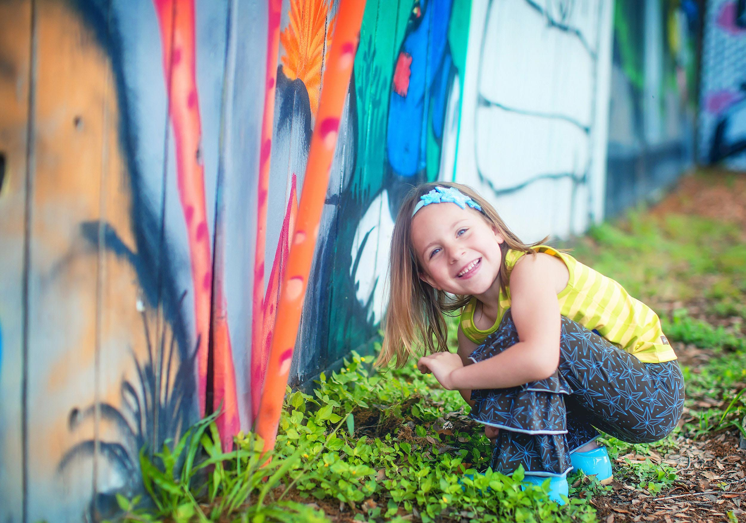 Colorful lifestyle portrait of little girl by art walls in Houston by spryART photography.
